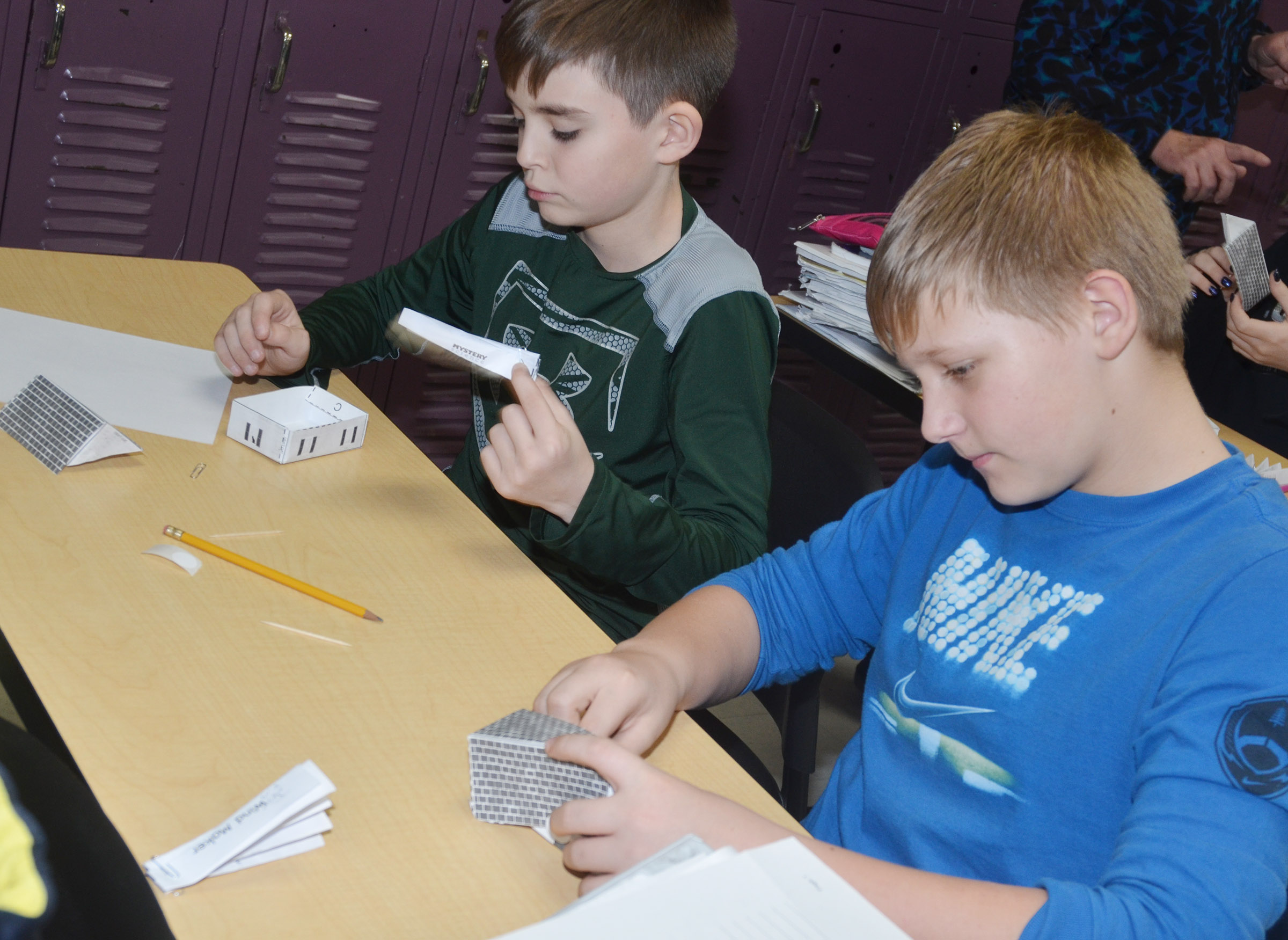 CMS sixth-graders Zachary Johnson, at left, and Jesse King work together to design and build their windproof houses.
