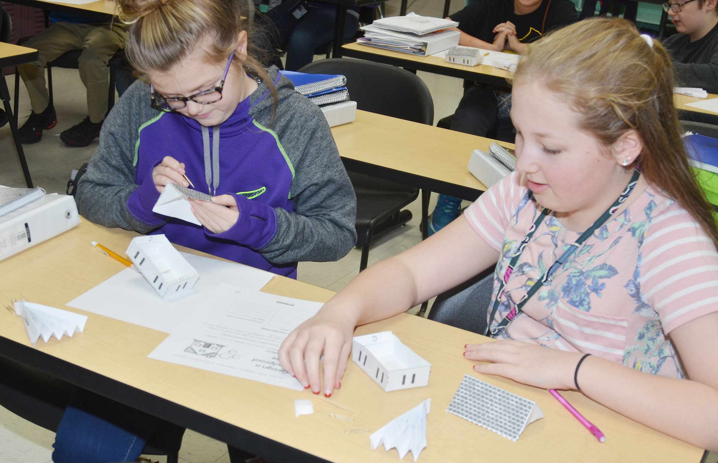 CMS sixth-graders Ellington Gowin, at left, and Ava Hughes work together to design and build their windproof houses.