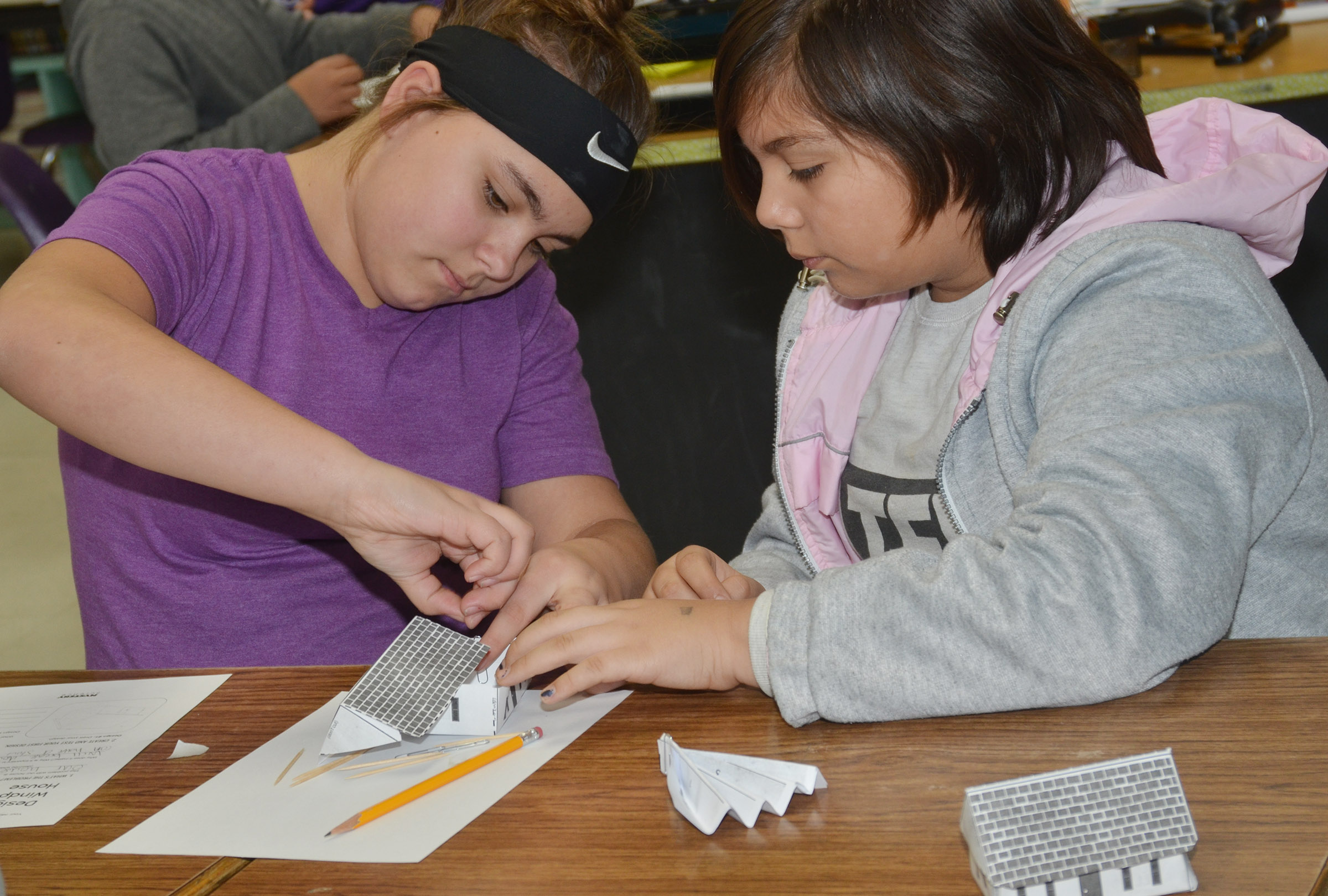 CMS sixth-graders Brooklyn Mays, at left, and Aaliyah Nunez work together to design and build their windproof houses.