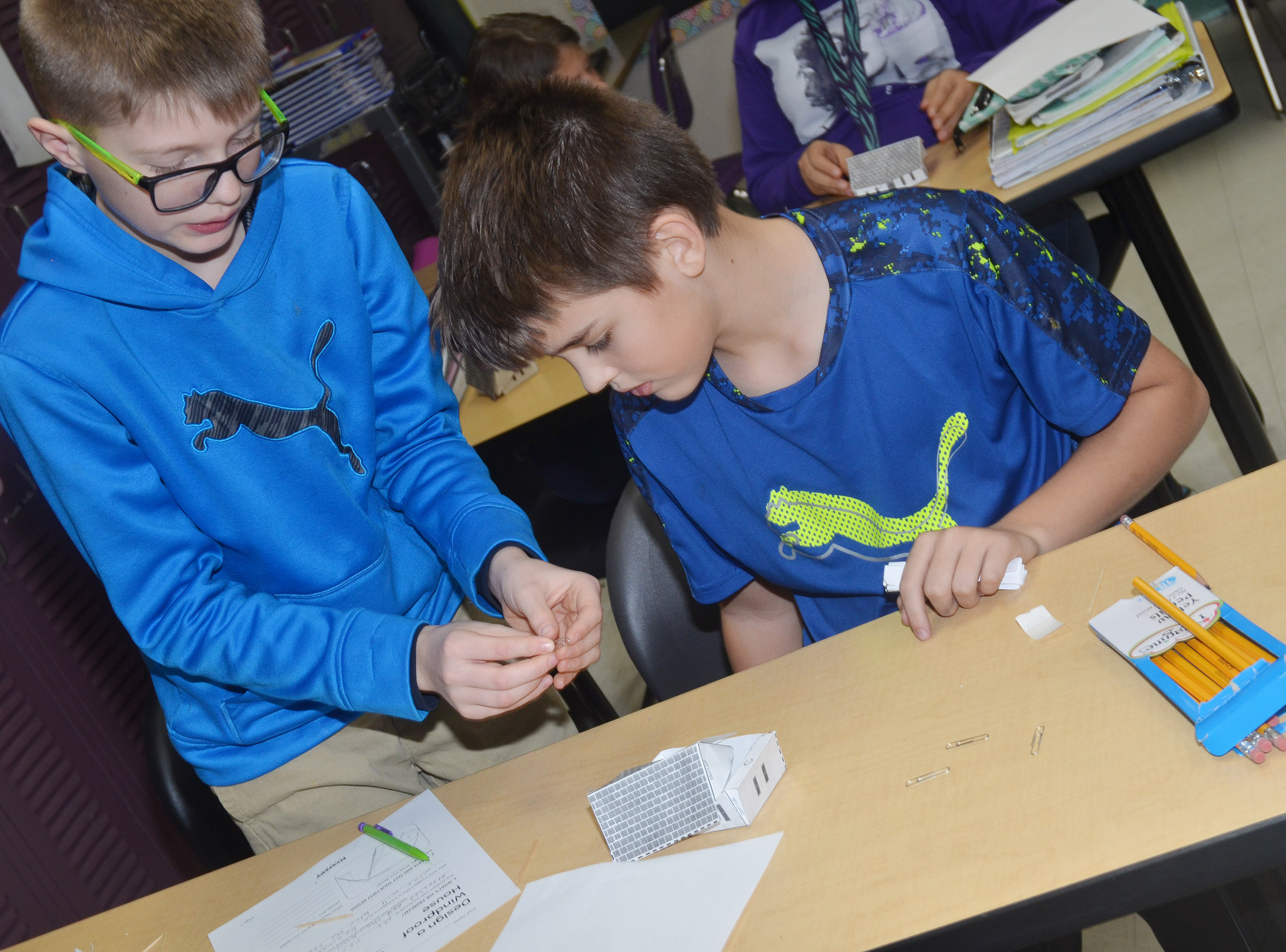 CMS sixth-graders Ethan Cox, at left, and Kaden Bloyd work to make their houses windproof.