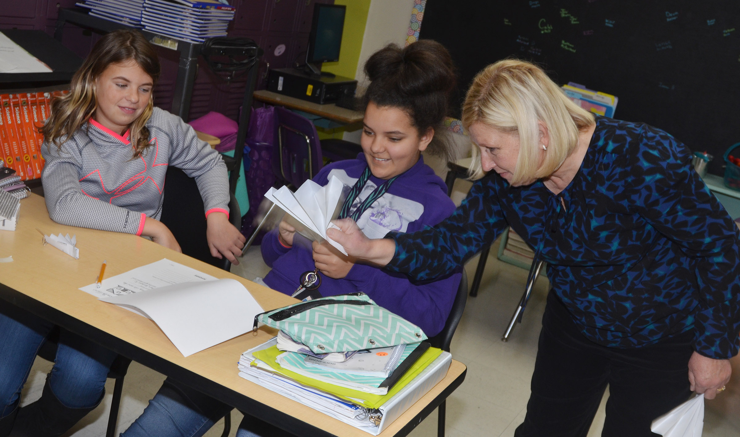 CMS sixth-grade teacher Jan Speer tests Aryanna Britton's and Gracie Taylor's house to see if it's windproof.