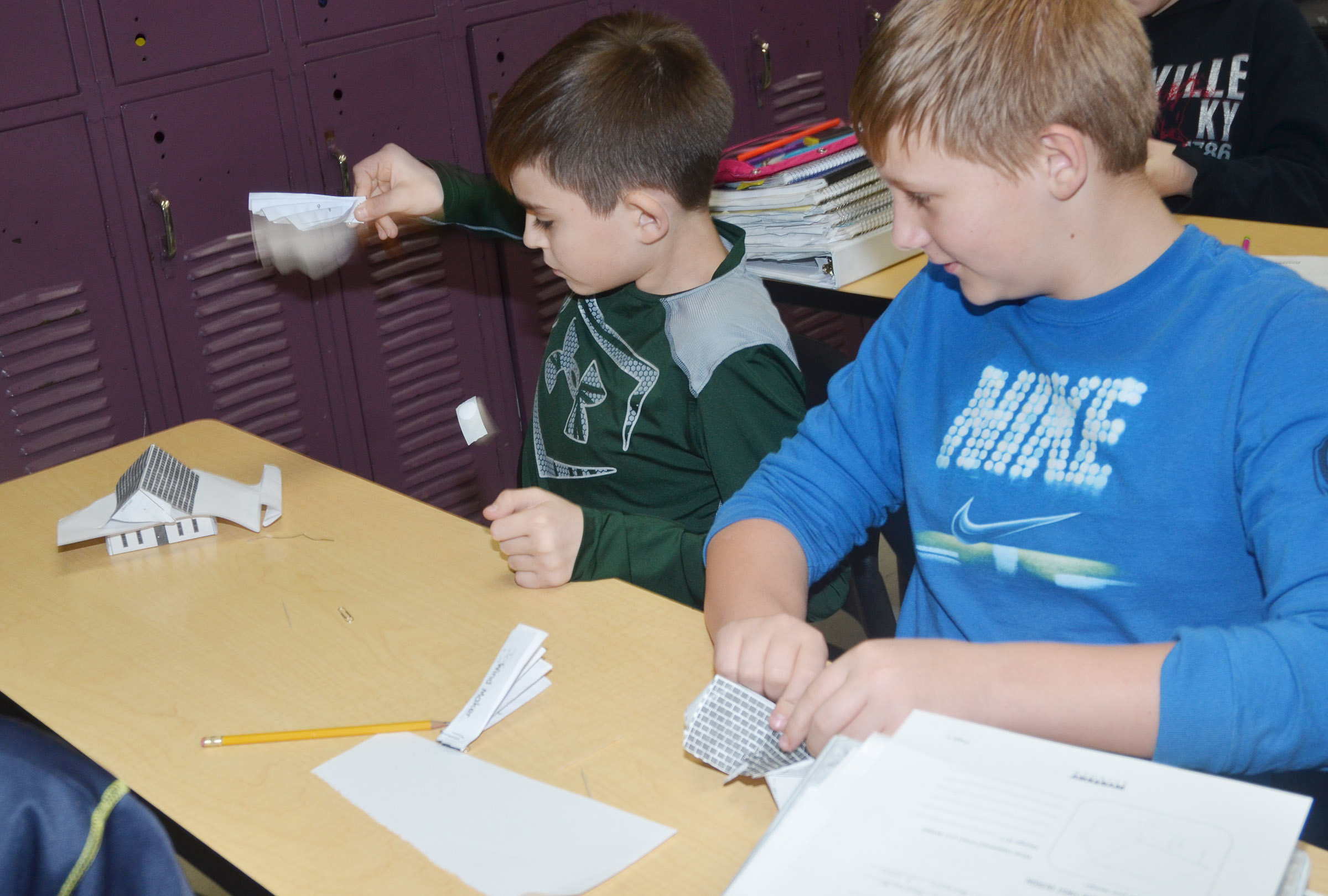 CMS sixth-graders Zachary Johnson, at left, and Jesse King test their houses to see if they are windproof.