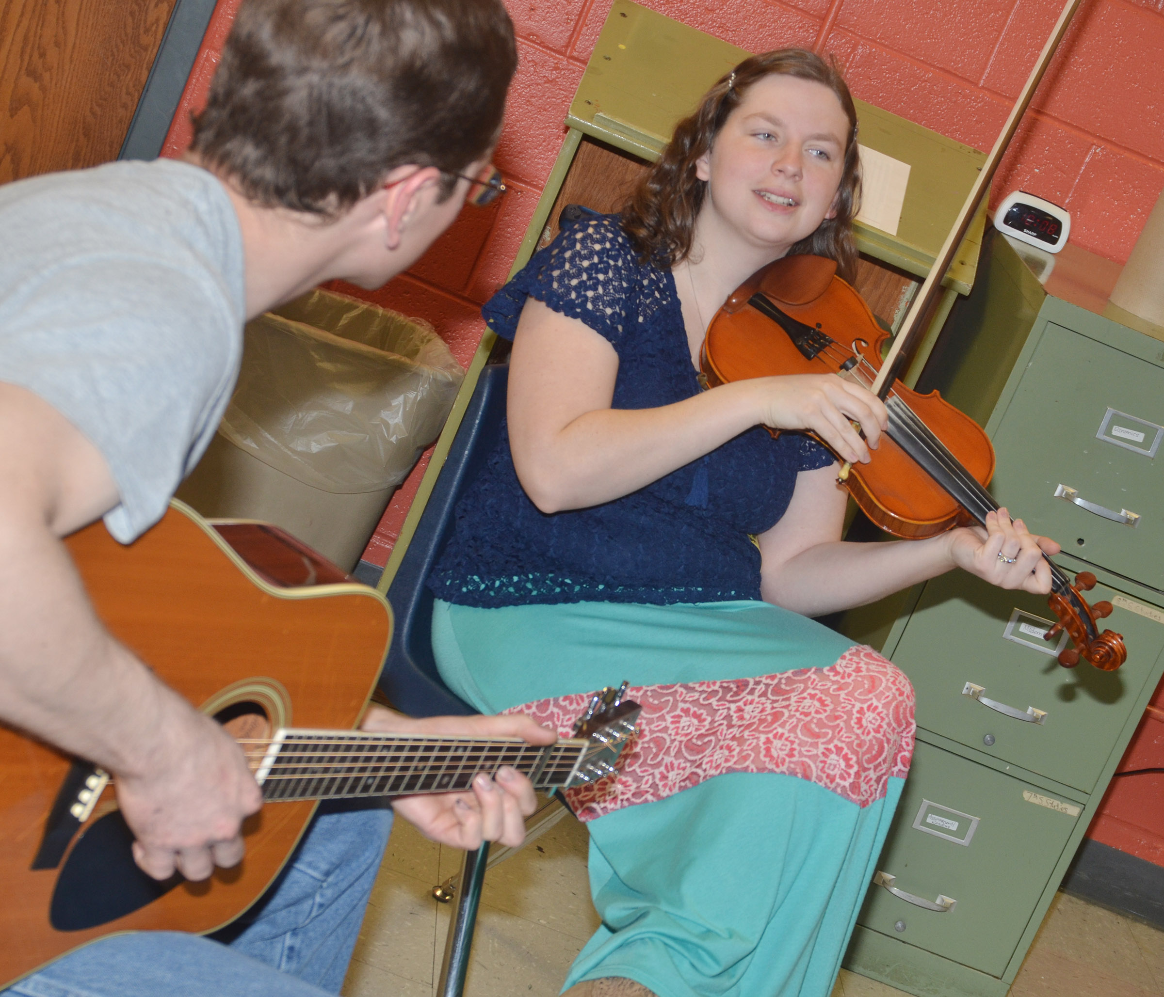 Local musicians Alex Vaughn, at left, and Jenny Beams play folk music as CMS students try out square dancing.