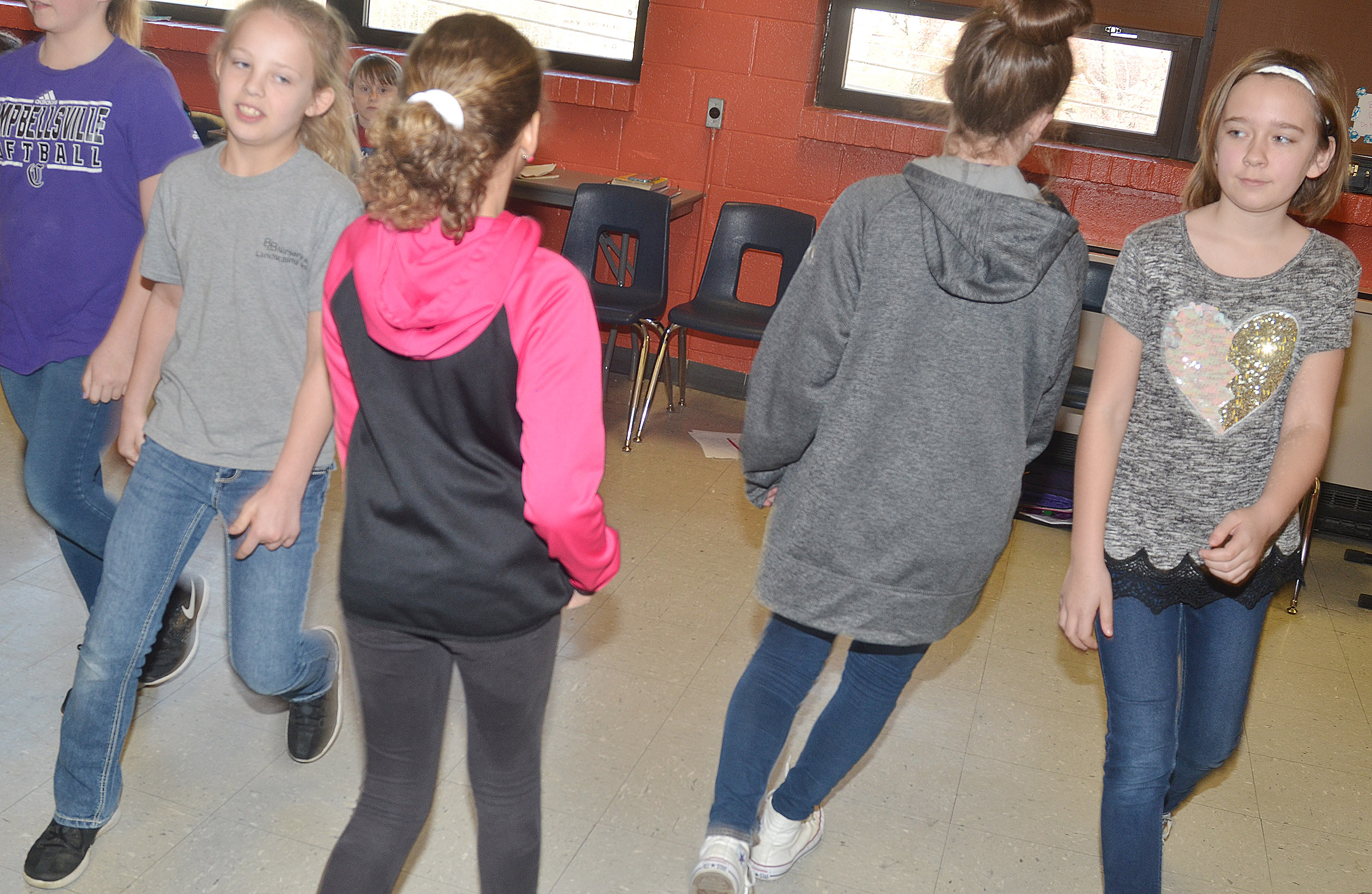 CMS sixth-grader Gabrielle Bright, at left, and fourth-grader Isabel Dengel dance with their partners.