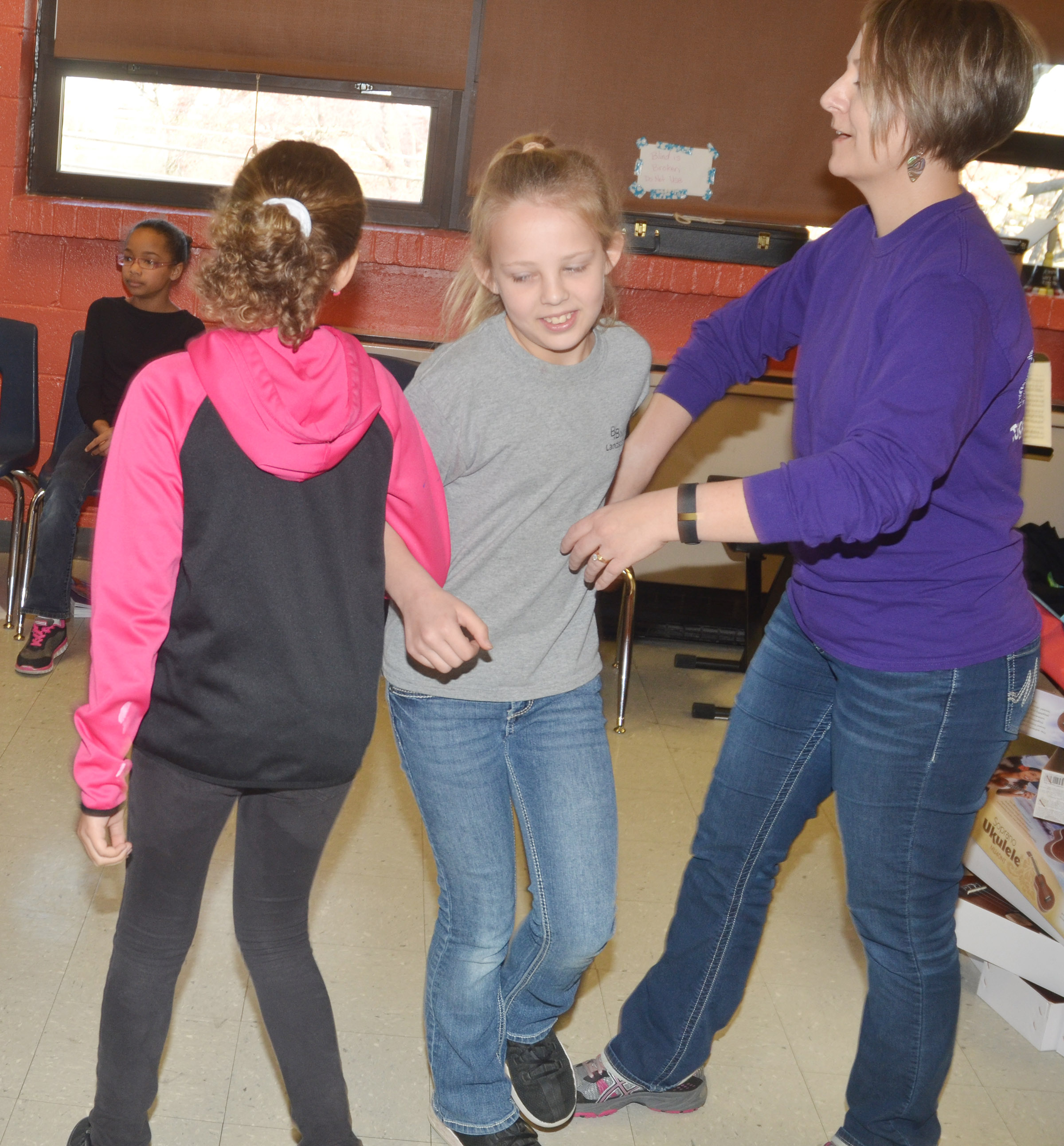 CMS music teacher Jessica Floyd helps sixth-grader Gabrielle Bright and her partner, fifth-grader Arisha Francis, dance.
