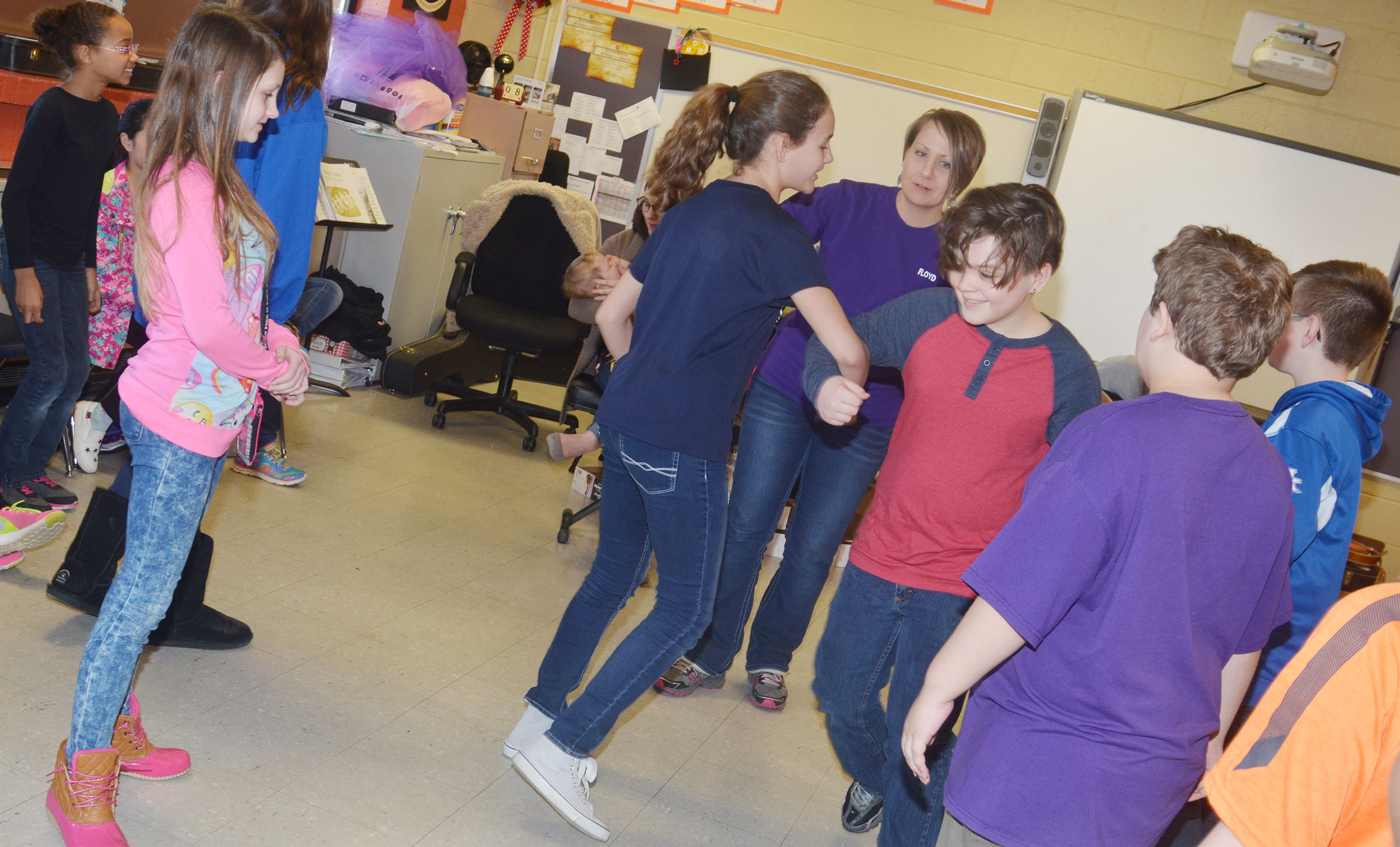 CMS music teacher Jessica Floyd helps her students, sixth-grader Haylee Allen and fifth-grader Kayden Birdwell, learn to square dance.