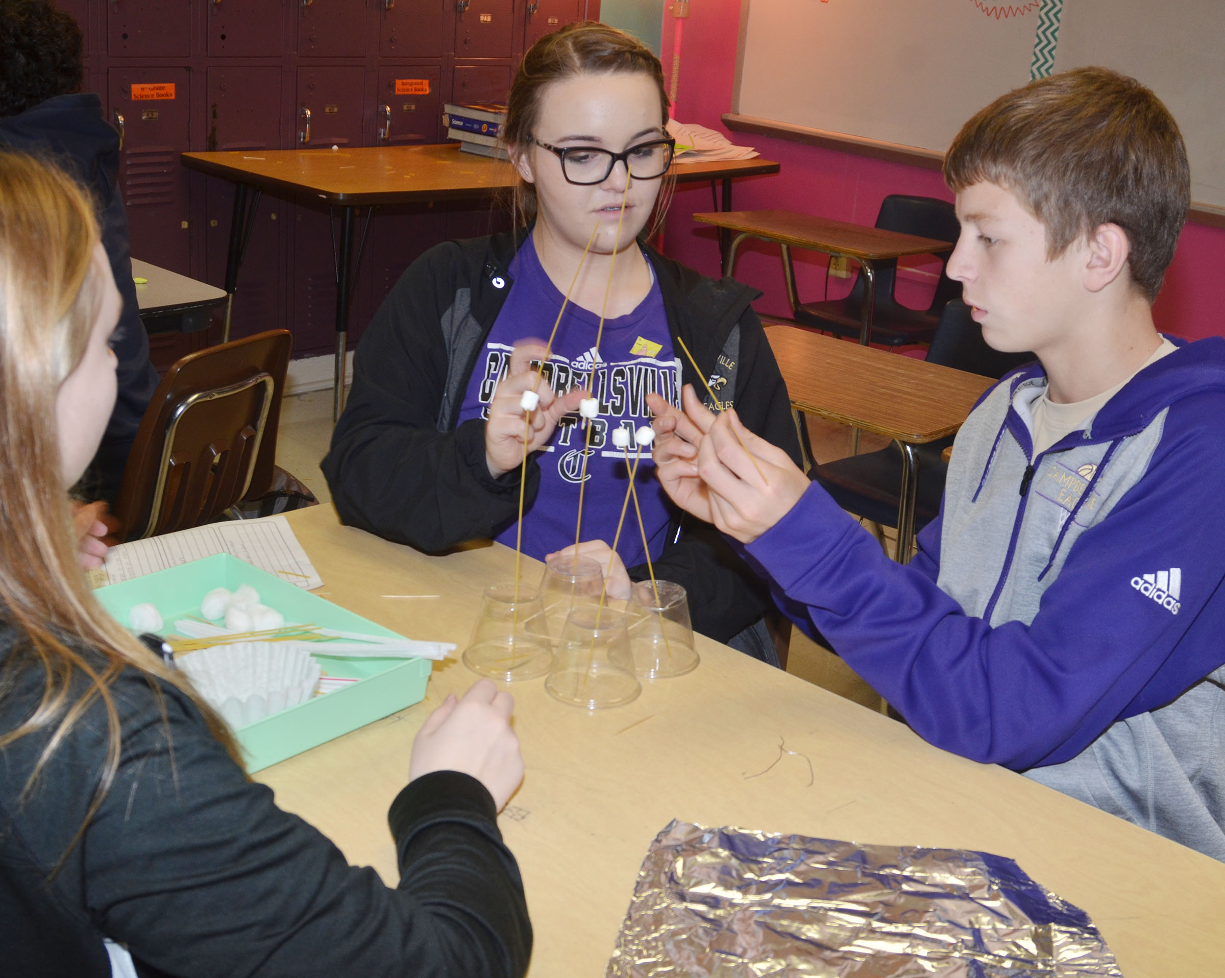 From left, CMS eighth-graders Catlyn Clausen and Kenzi Forbis and CHS freshman Noah Hughes build their structure with spaghetti and marshmallows.
