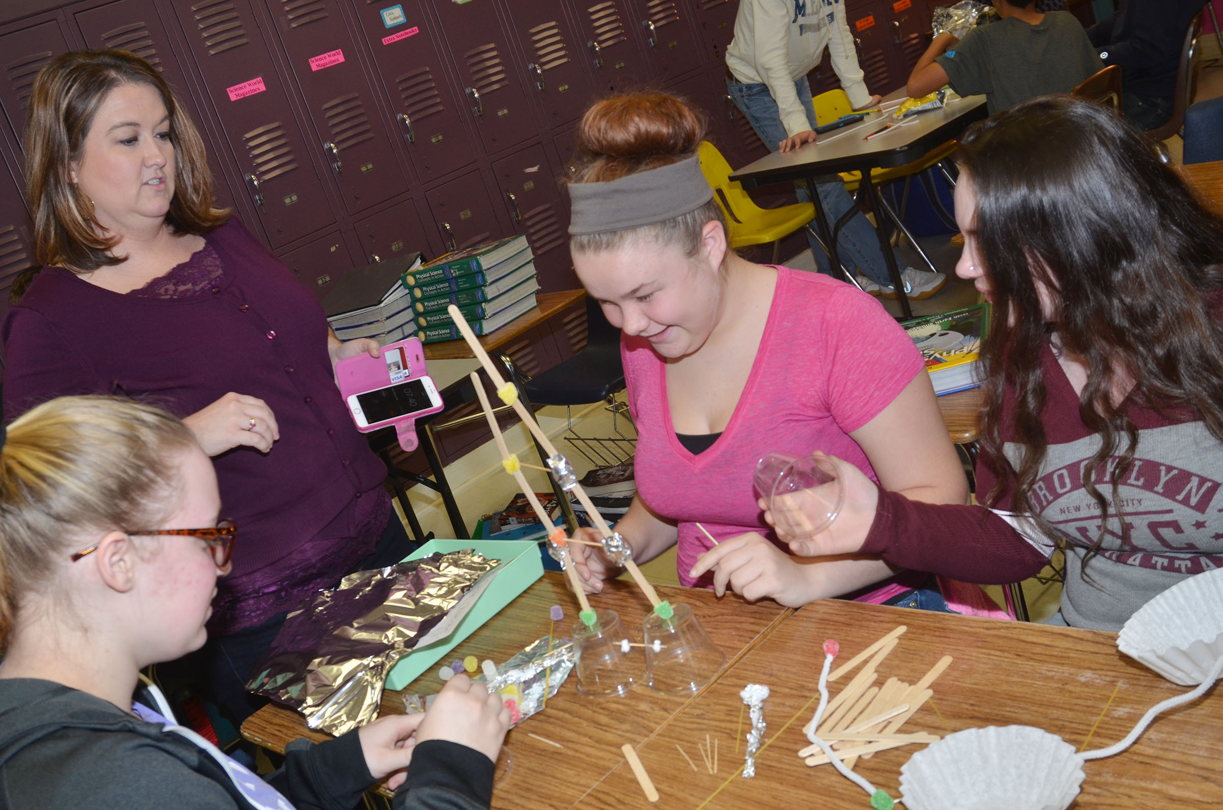 CMS integrated science teacher Amy Knifley watches as, from left, freshman Samantha Johnson, Summer Sluder and Summer Edwards build their structure with Popsicle sticks and gum drops.