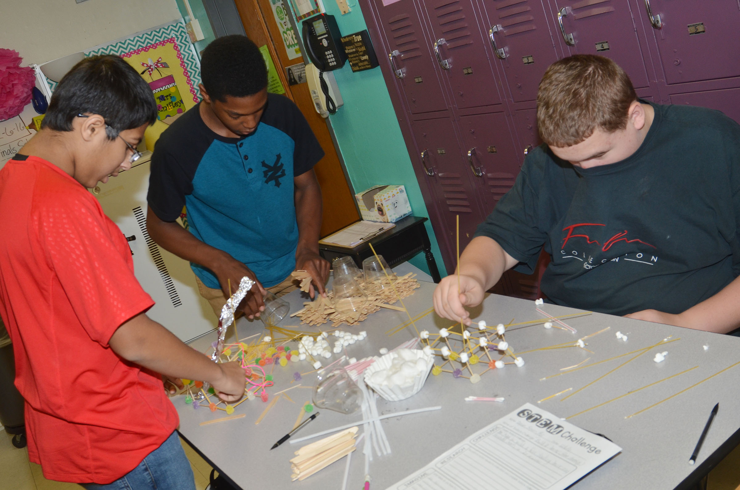 CMS eighth-graders, from left, Raj Patel, Zaquan Cowan and Steven James work together to build their structure.