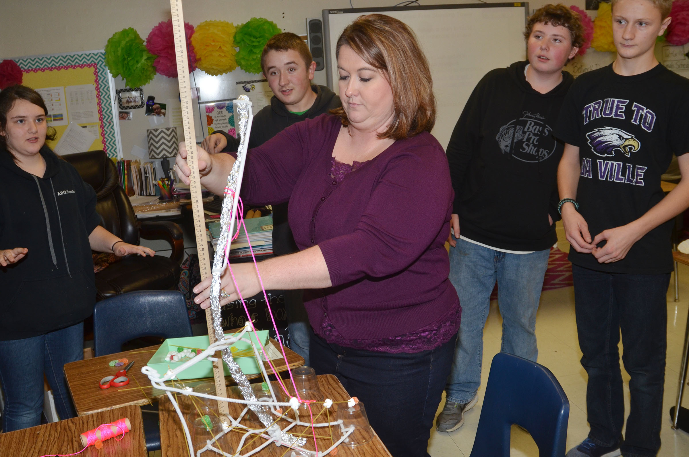 CMS integrated science teacher Amy Knifley measures to see if this structure, built by, from left, eighth-graders Haley Lopez, Zachary Shaw, Alex Howard and Jake Dicken, is the tallest.