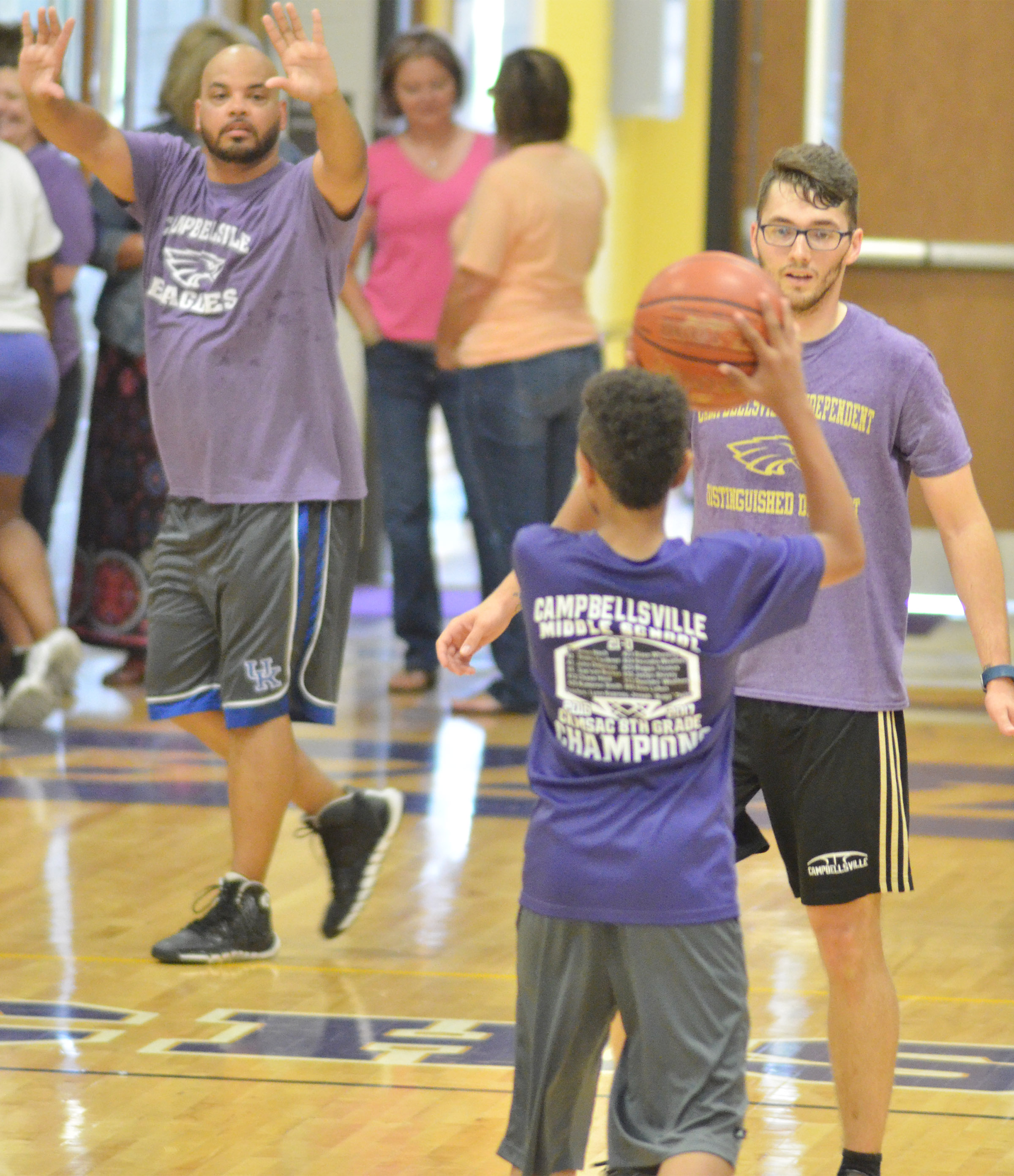 CMS eighth-grader Jastyn Shively looks to pass as Campbellsville Elementary School cafeteria worker Aaron Webb, at left, and Campbellsville High School instructional assistant Cody Wills guard him.