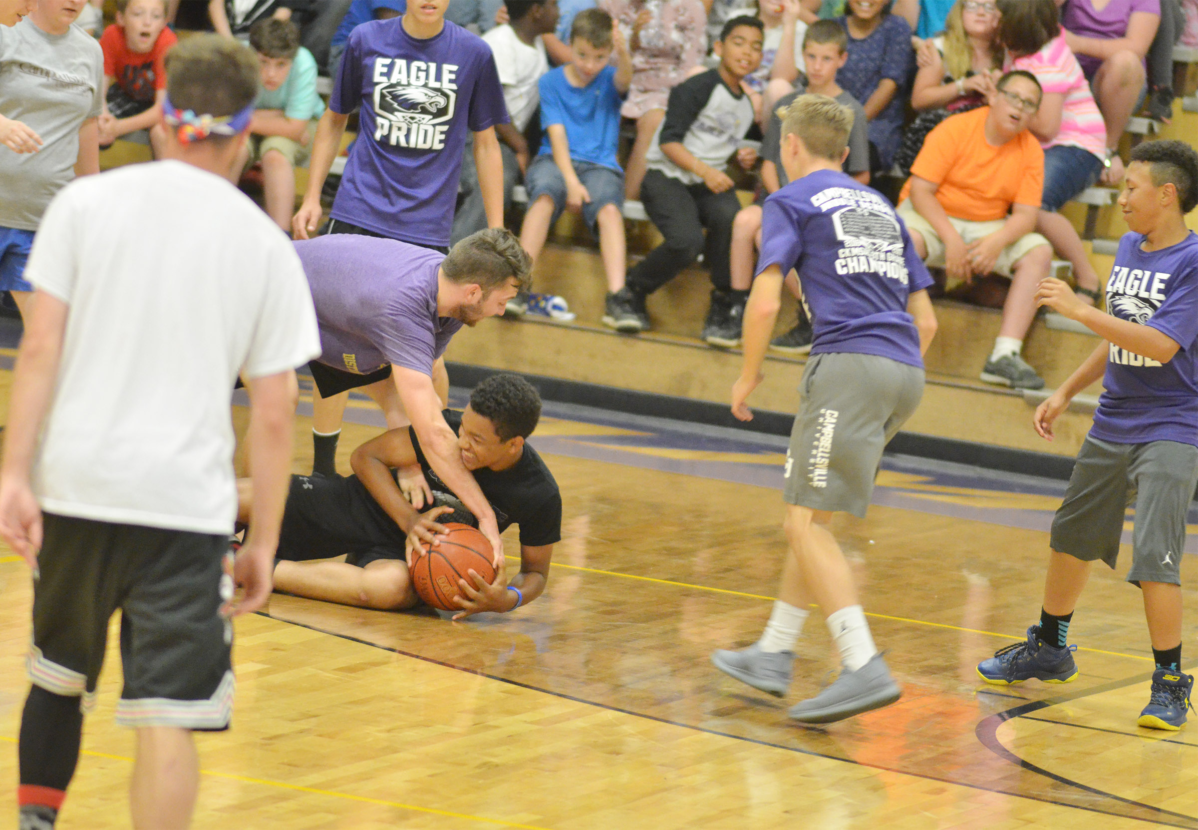 CMS eighth-grader Reggie Thomas battles Campbellsville High School instructional assistant Cody Wills for the ball.