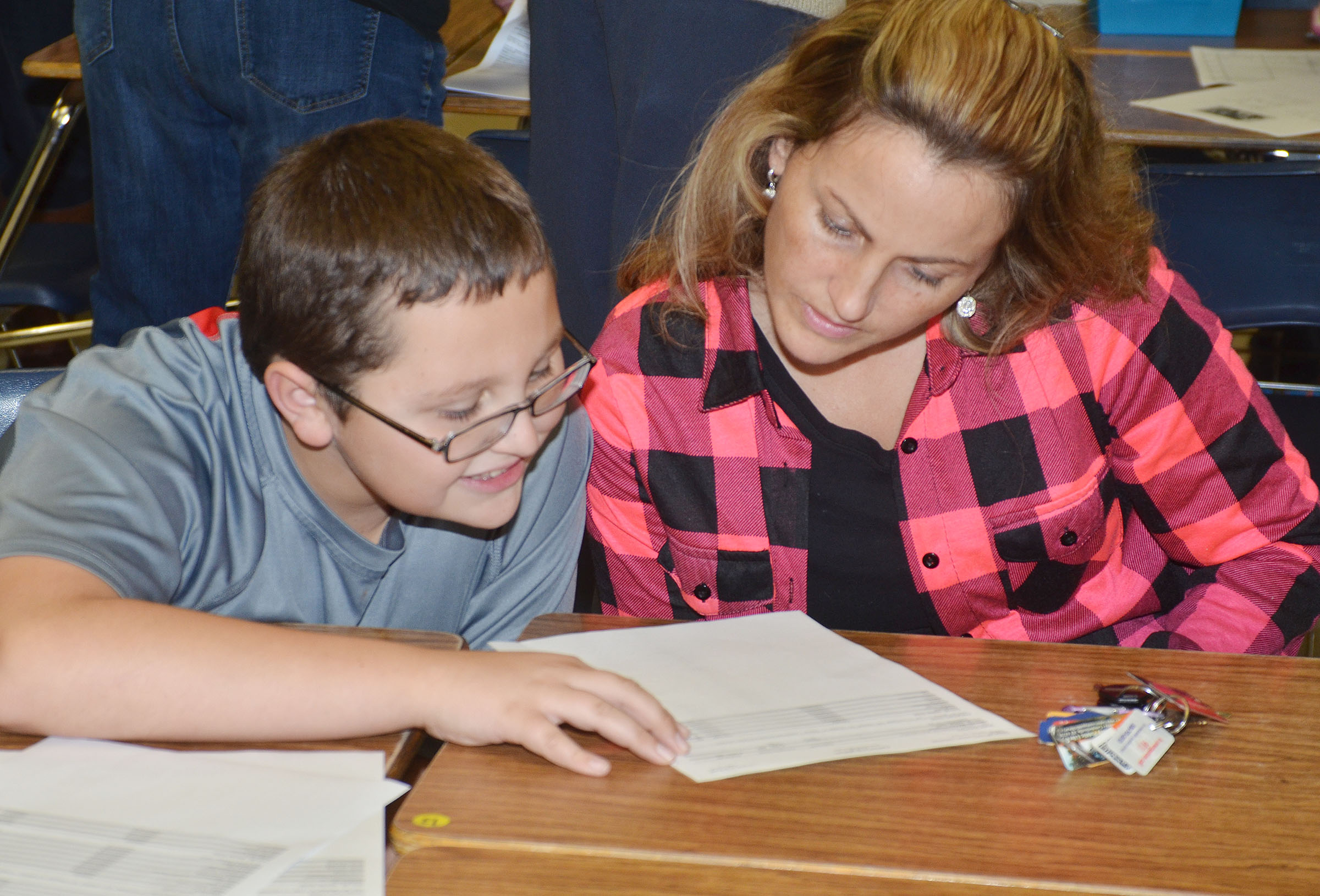 CMS sixth-grader Cameron Mahan looks at his grades with his mother, Latasha.