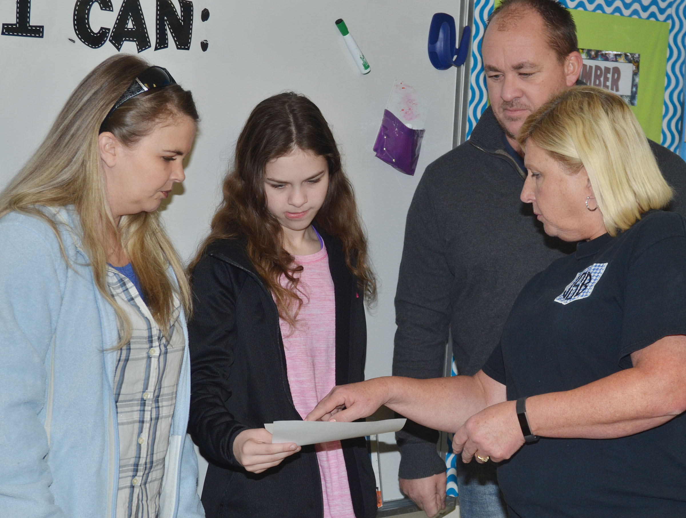 CMS sixth-grader Karlee Rakel looks at her grades with her parents, Eddie and Jaclyn, and one of her teachers, Jan Speer.