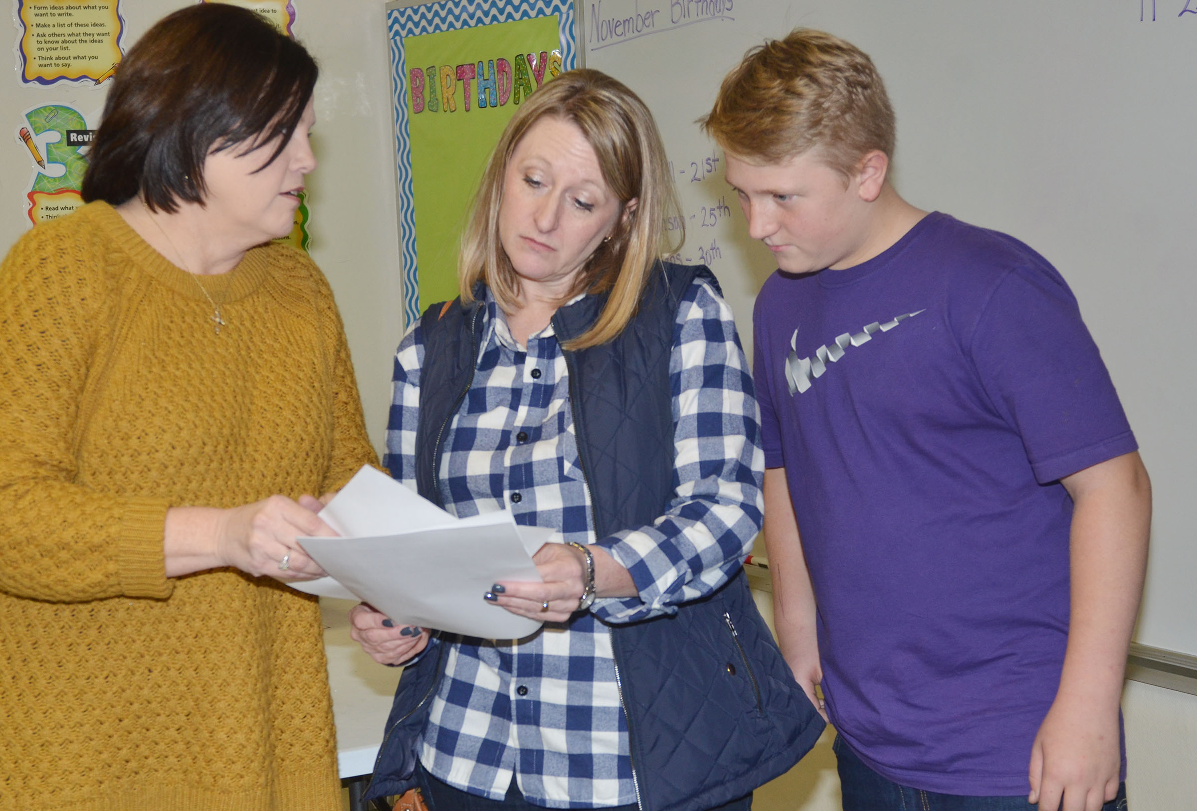 CMS sixth-grader Levi Dicken reviews his grades with his mother, Laura, and one of his teachers, Lisa Kearney.