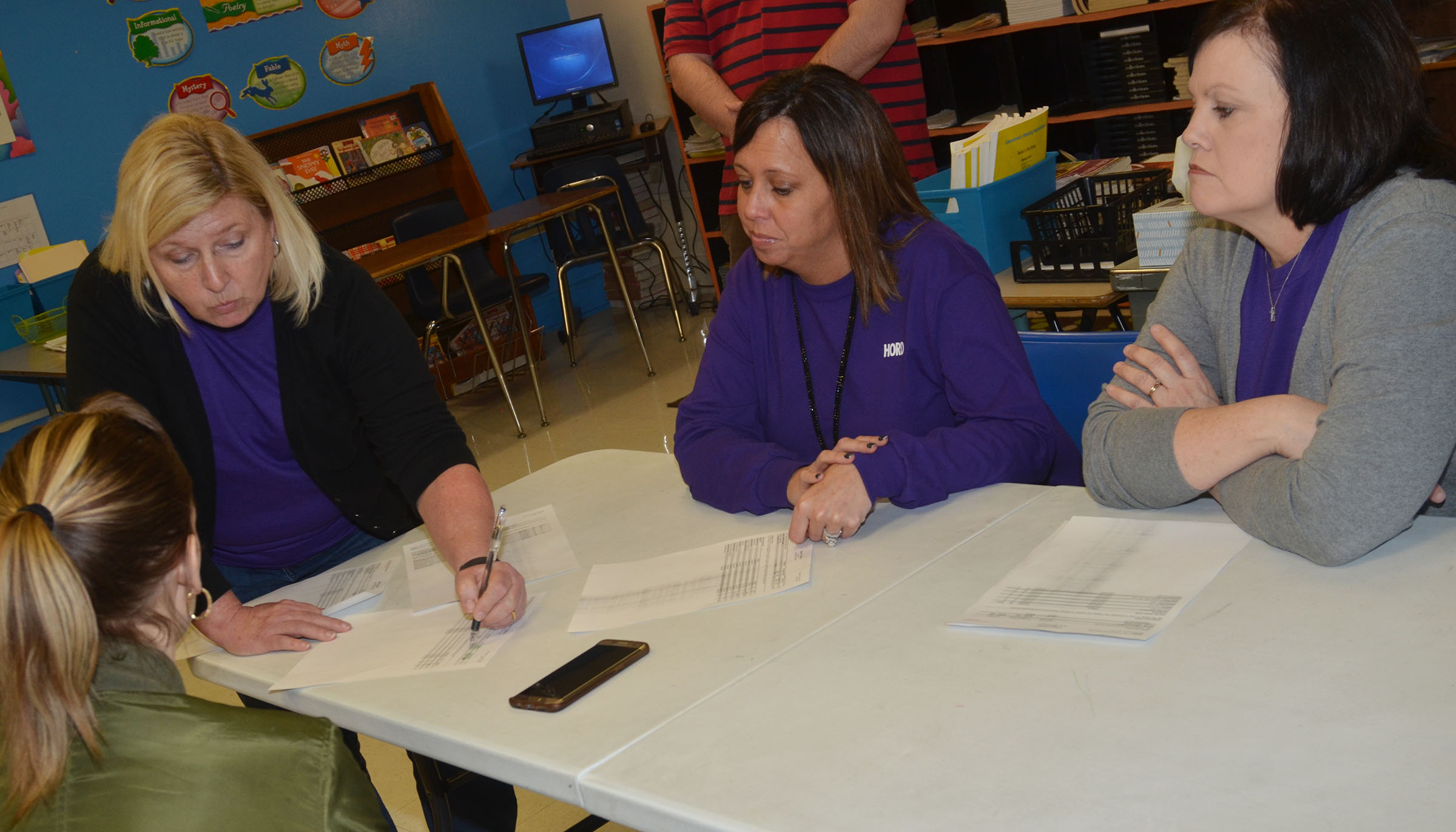 CMS sixth-grade teachers, from left, Jan Speer, Farrah Hord and Lisa Kearney talk to a parent about her son's grades.