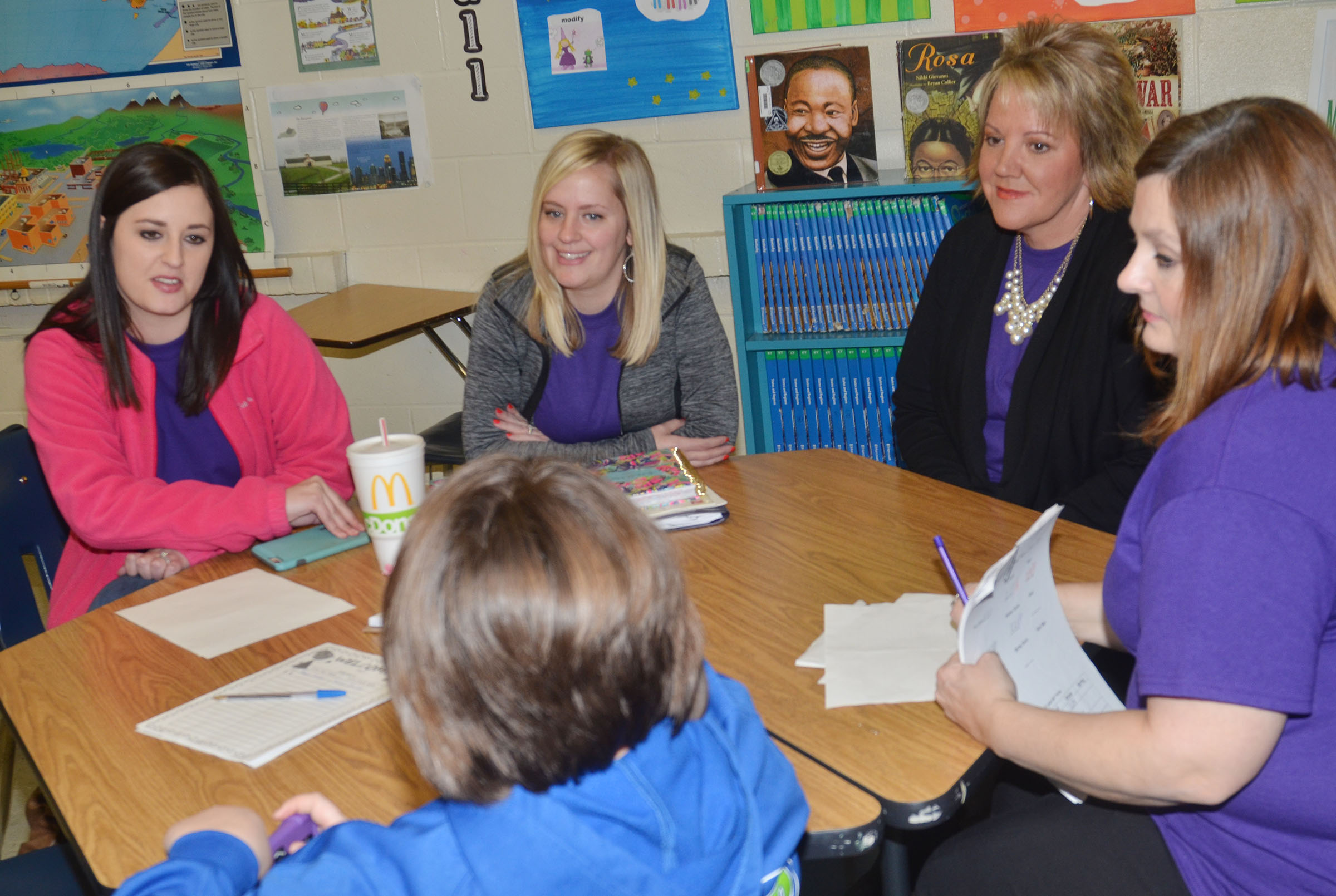 CMS fourth-grade teachers, from left, Samantha Coomer, Maranda Wright, Kaye Agathen and Garnetta Murrell talk to a student about her grades.