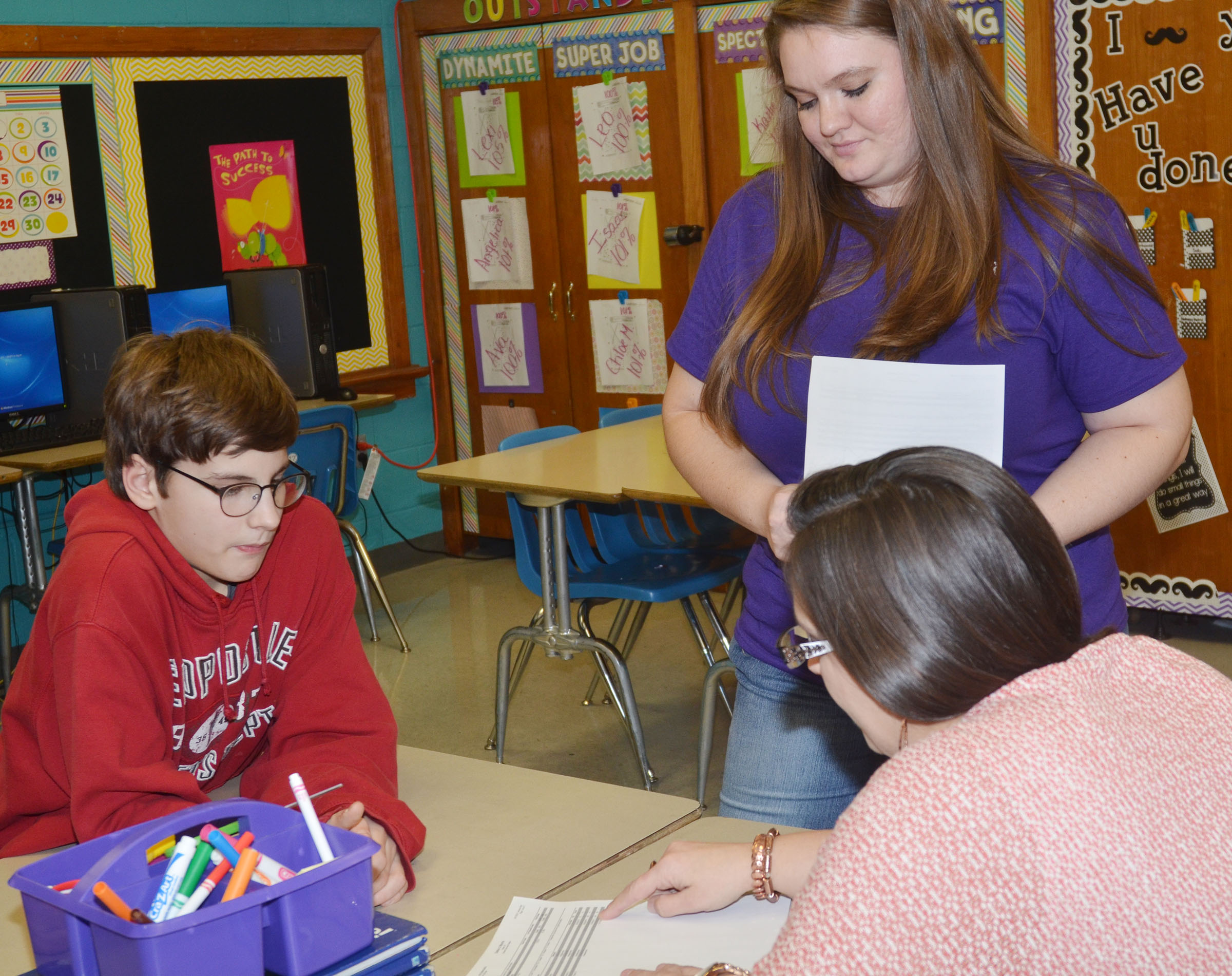 CMS fifth-grade teacher Ann Michael Tucker talks to Dalton Morris and his mother, Shannon, about his grades.