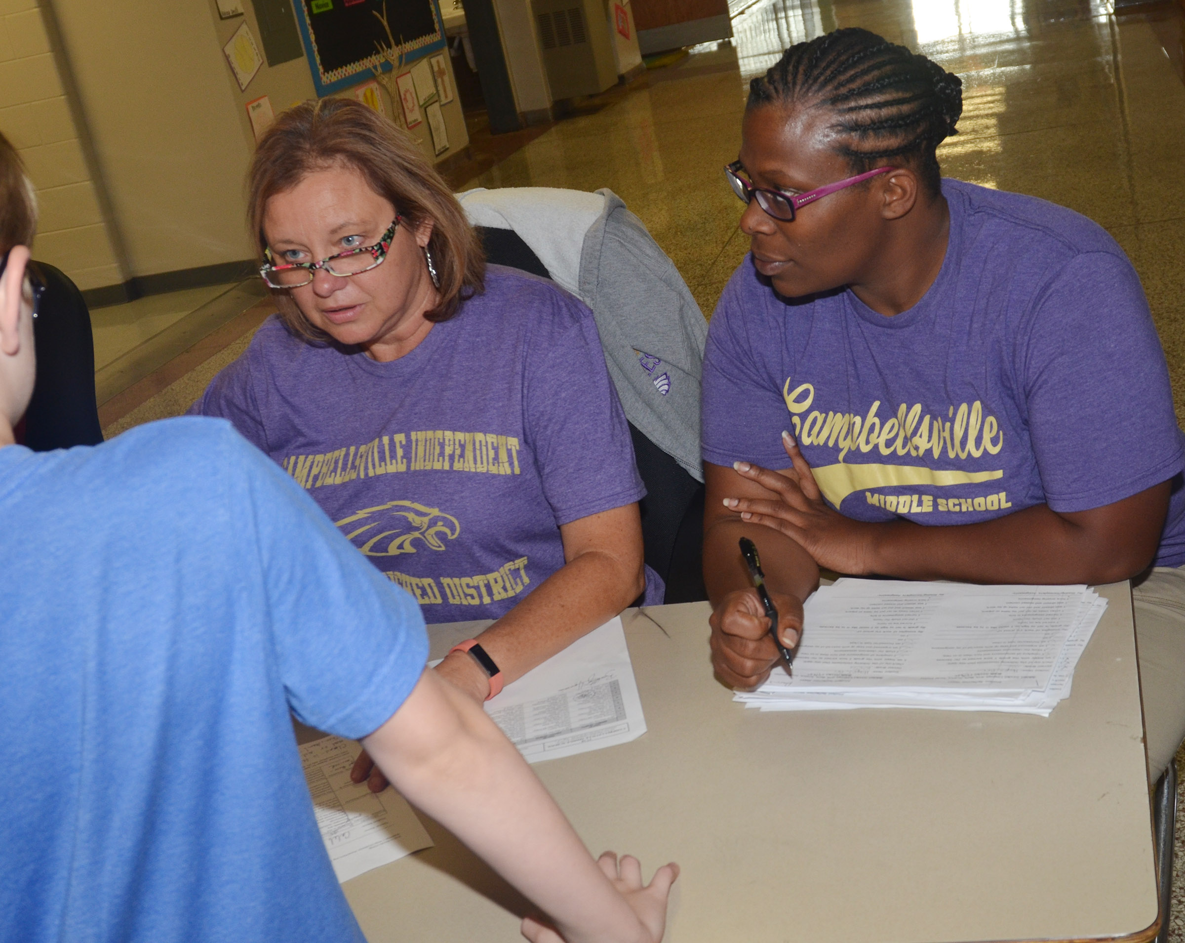 CMS teachers Sharon Harris, at left, and Tiarra Cecil talk with parents.