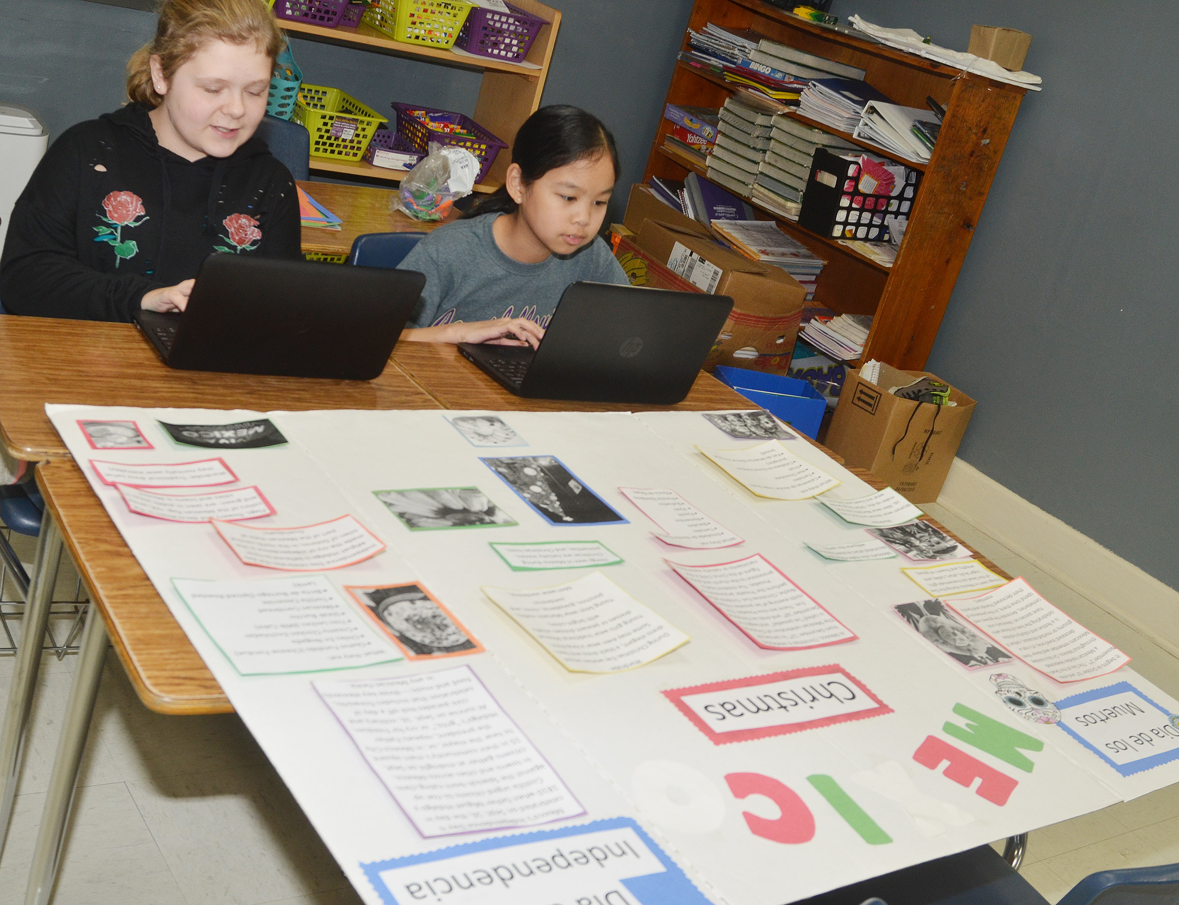CMS sixth-graders Alexis Sharp, at left, and Angelica Seng work on a class project.