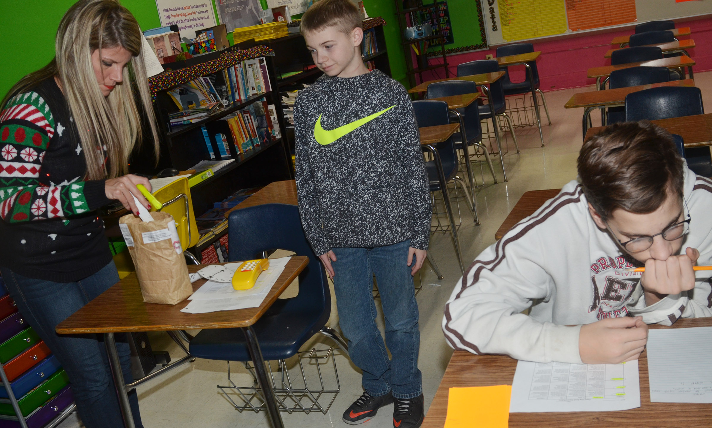 CMS teacher Andrea Gribbins works with sixth-graders Ethan Cox, at left, and Dalton Morris on their assignments.