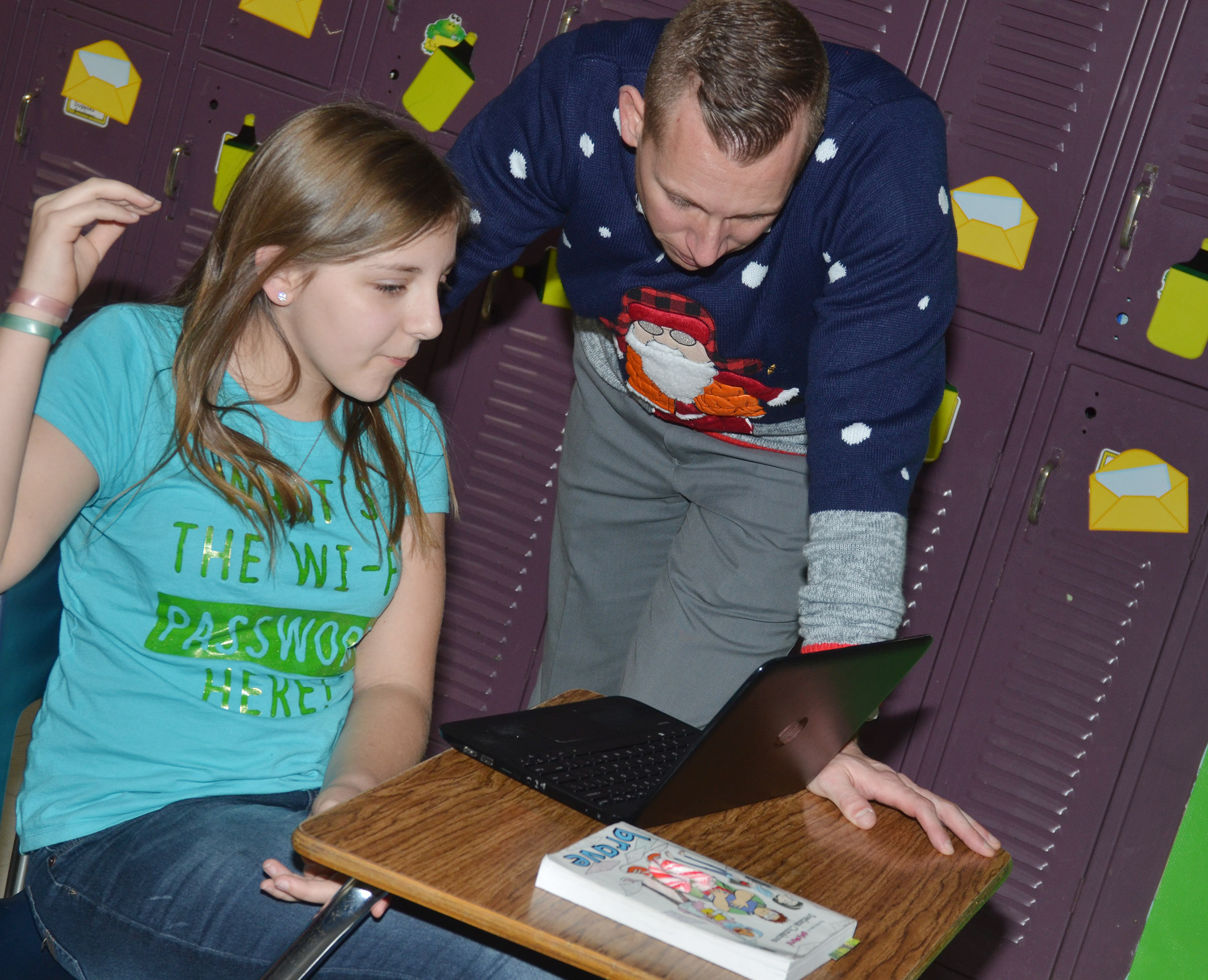 CMS Principal Zach Lewis works with sixth-grader Grace Tungate.