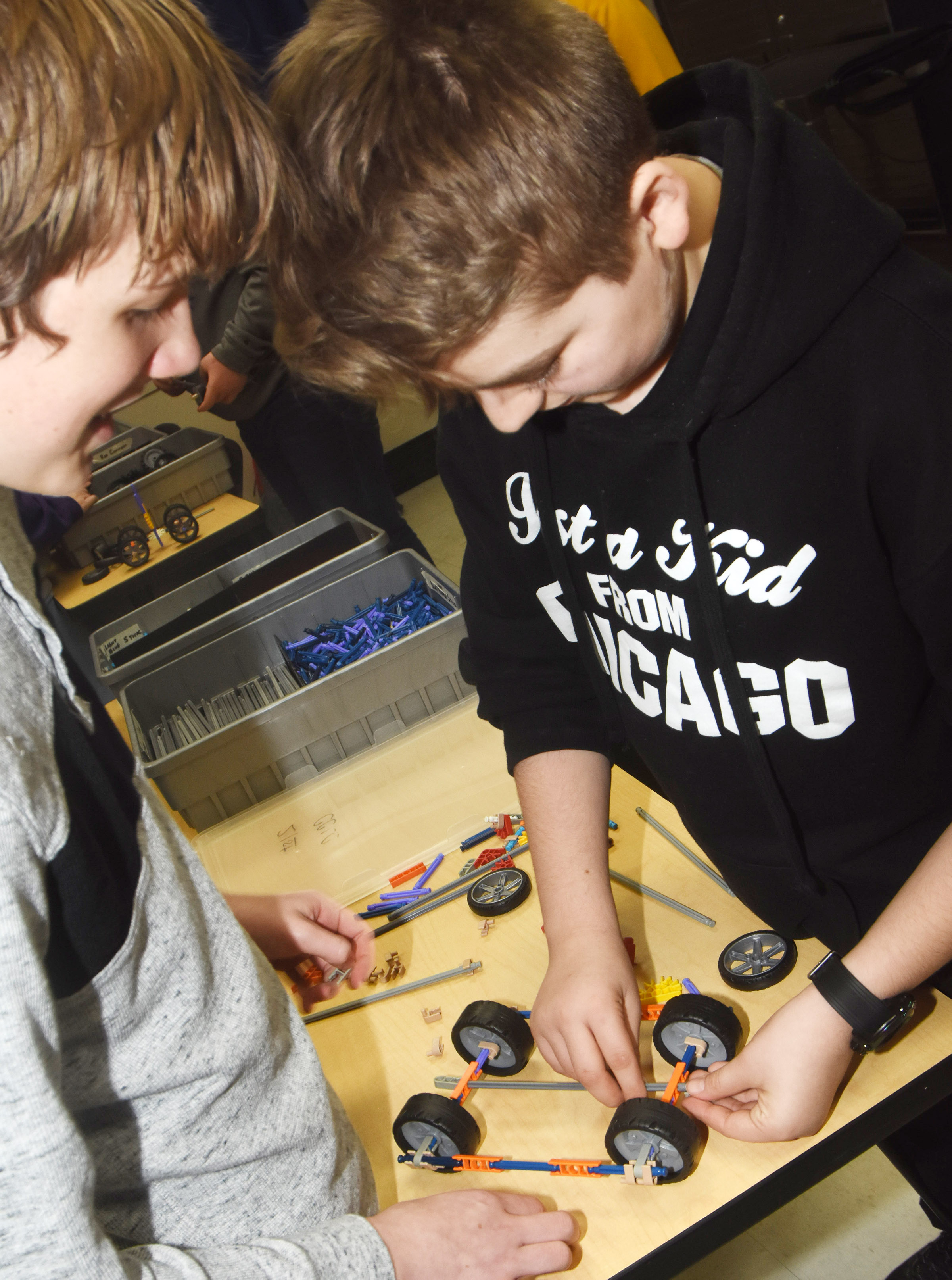 CMS seventh-graders Thomas Lucas, at left, and Nathan McFarland build a wind-powered car.