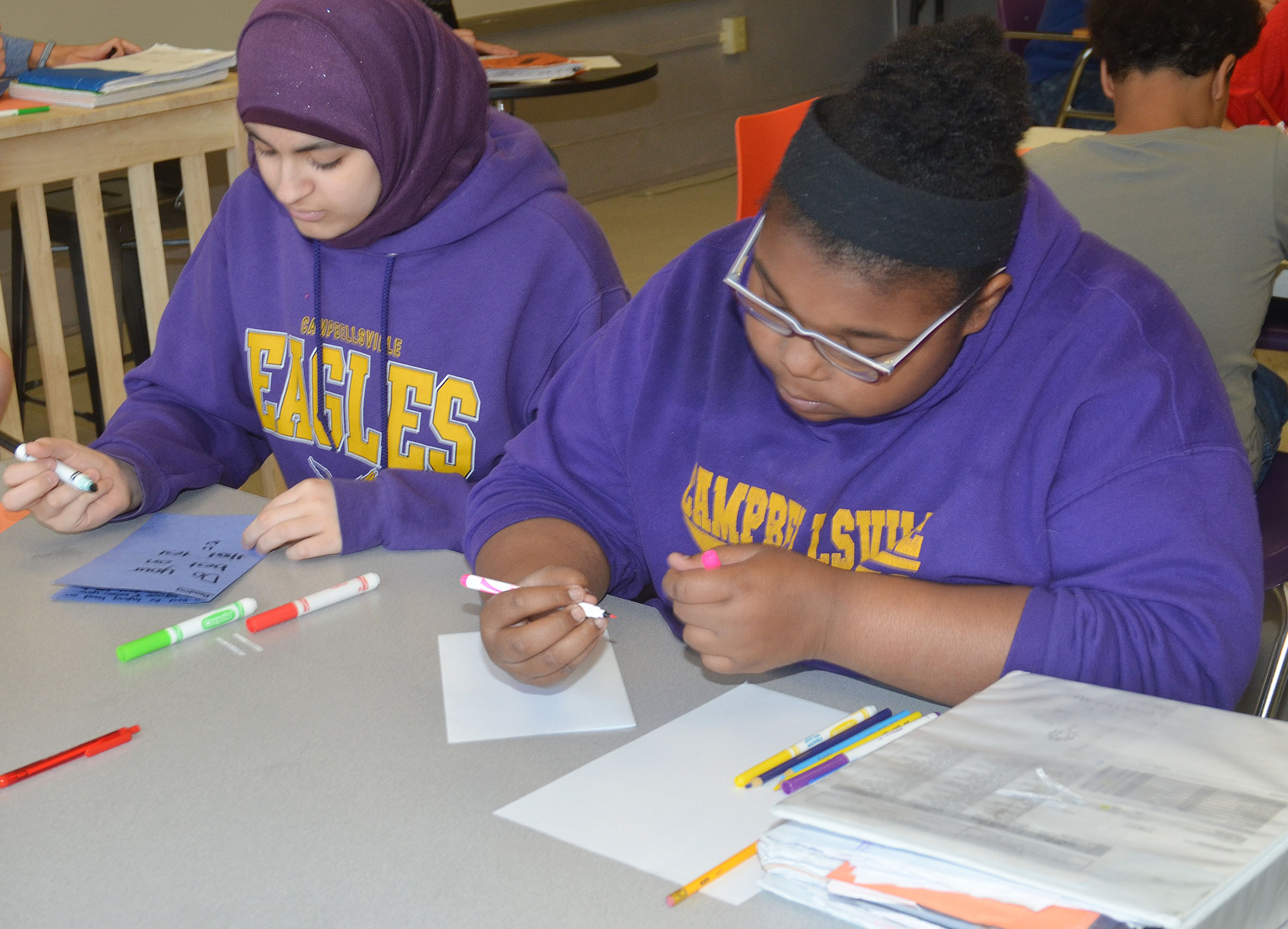 CMS eighth-graders Yasmeen El-Amouri, at left, and Destany Lane write good luck cards for their classmates.