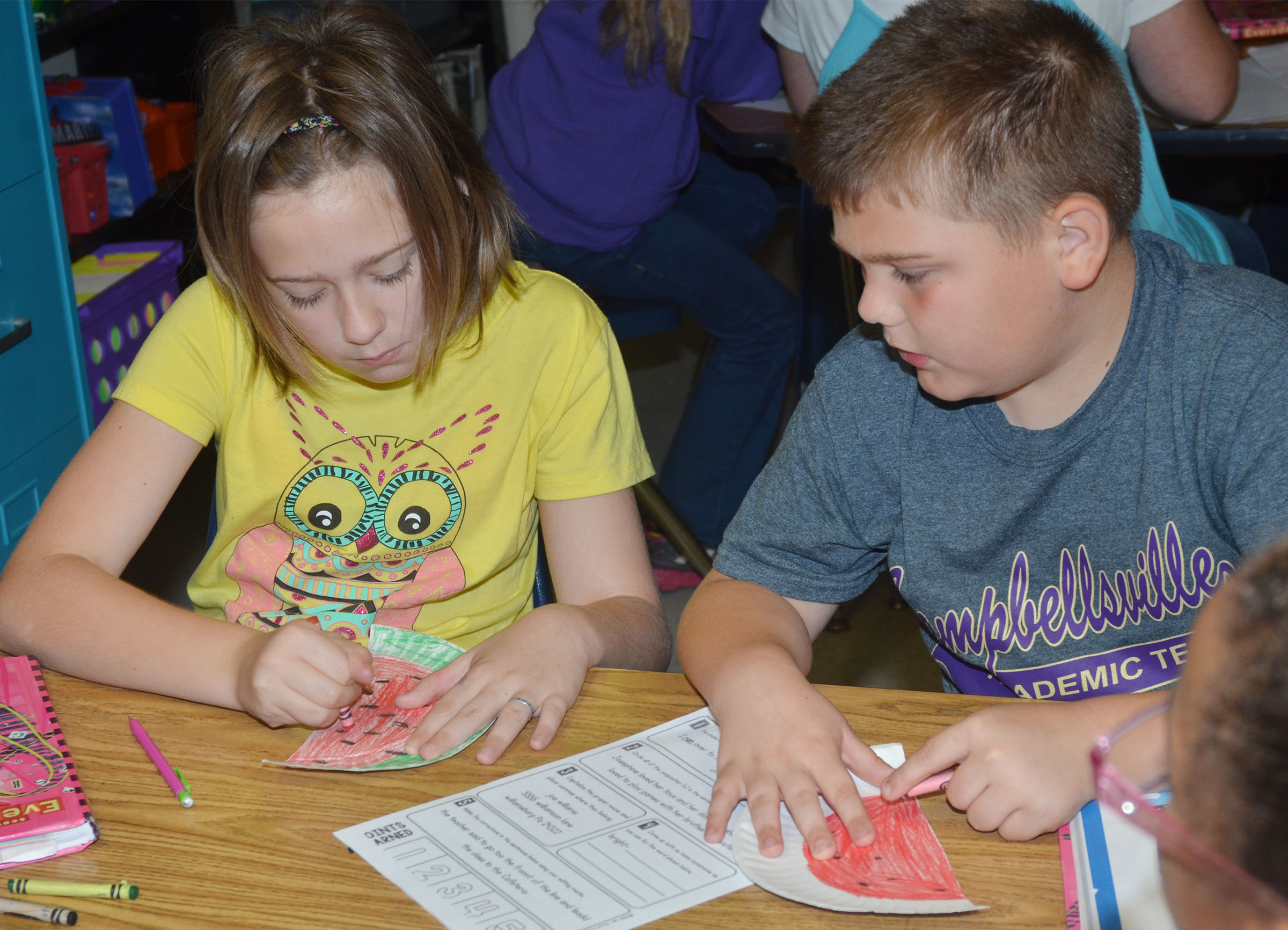 CMS fourth-graders Isabel Dengel, at left, and Logan England color their watermelons.