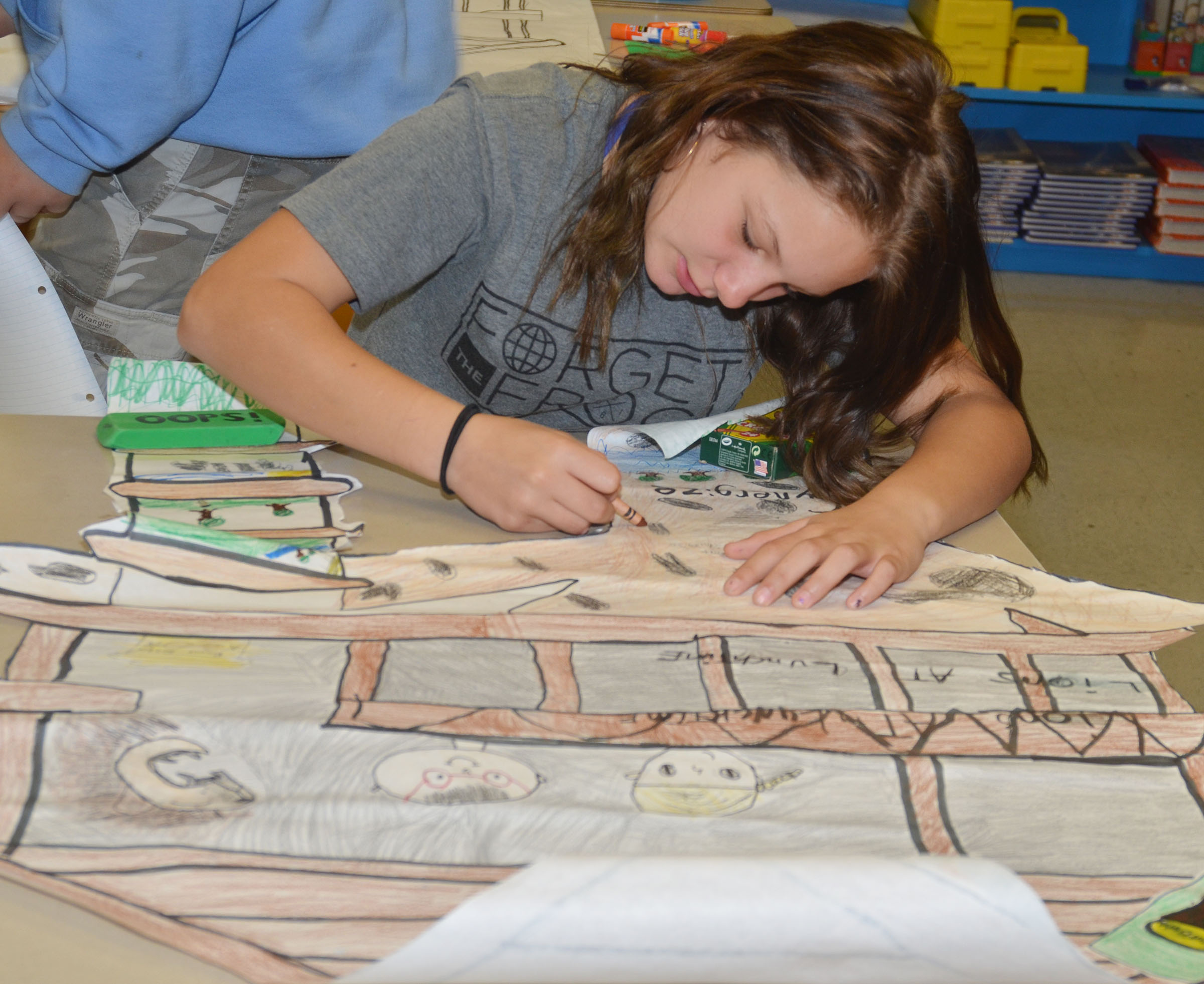 CMS fifth-grader Margaret Johnson colors her group's treehouse project.