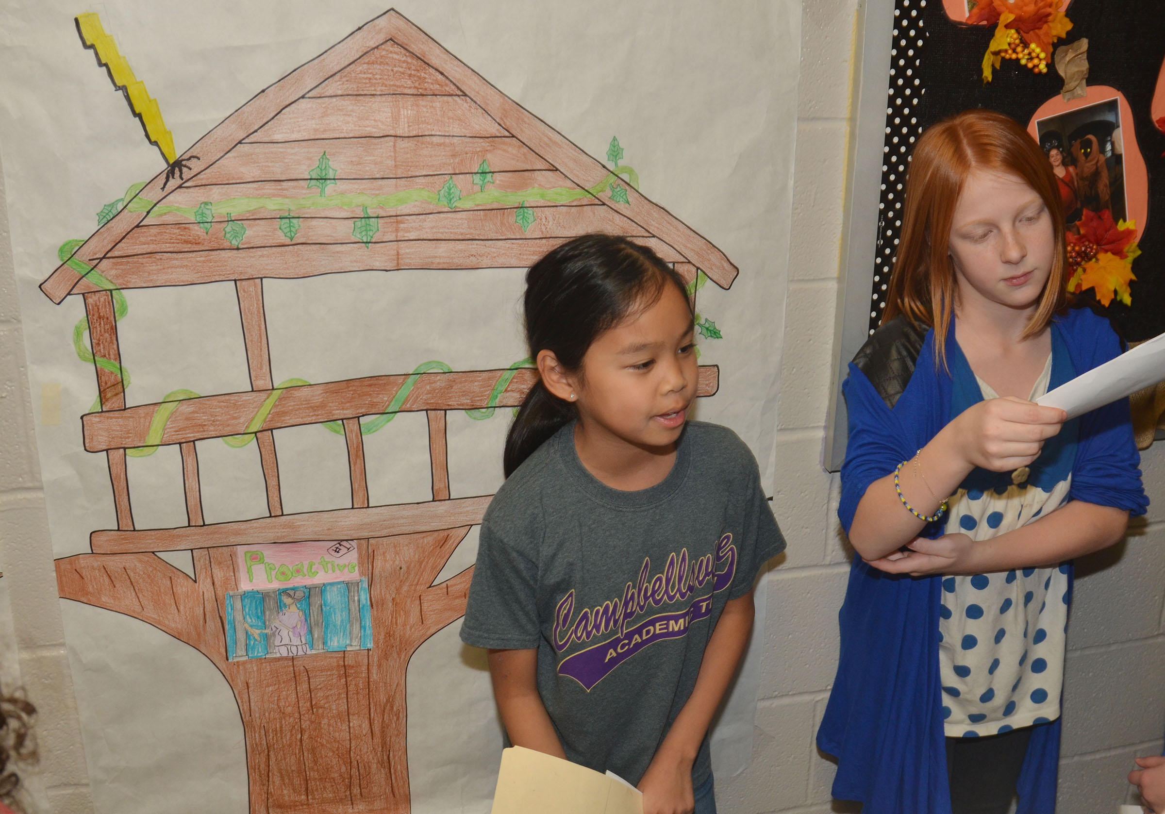 CMS fifth-graders Angelica Seng, at left, and Kaydence Wethington present their treehouse project to fourth-grade students.
