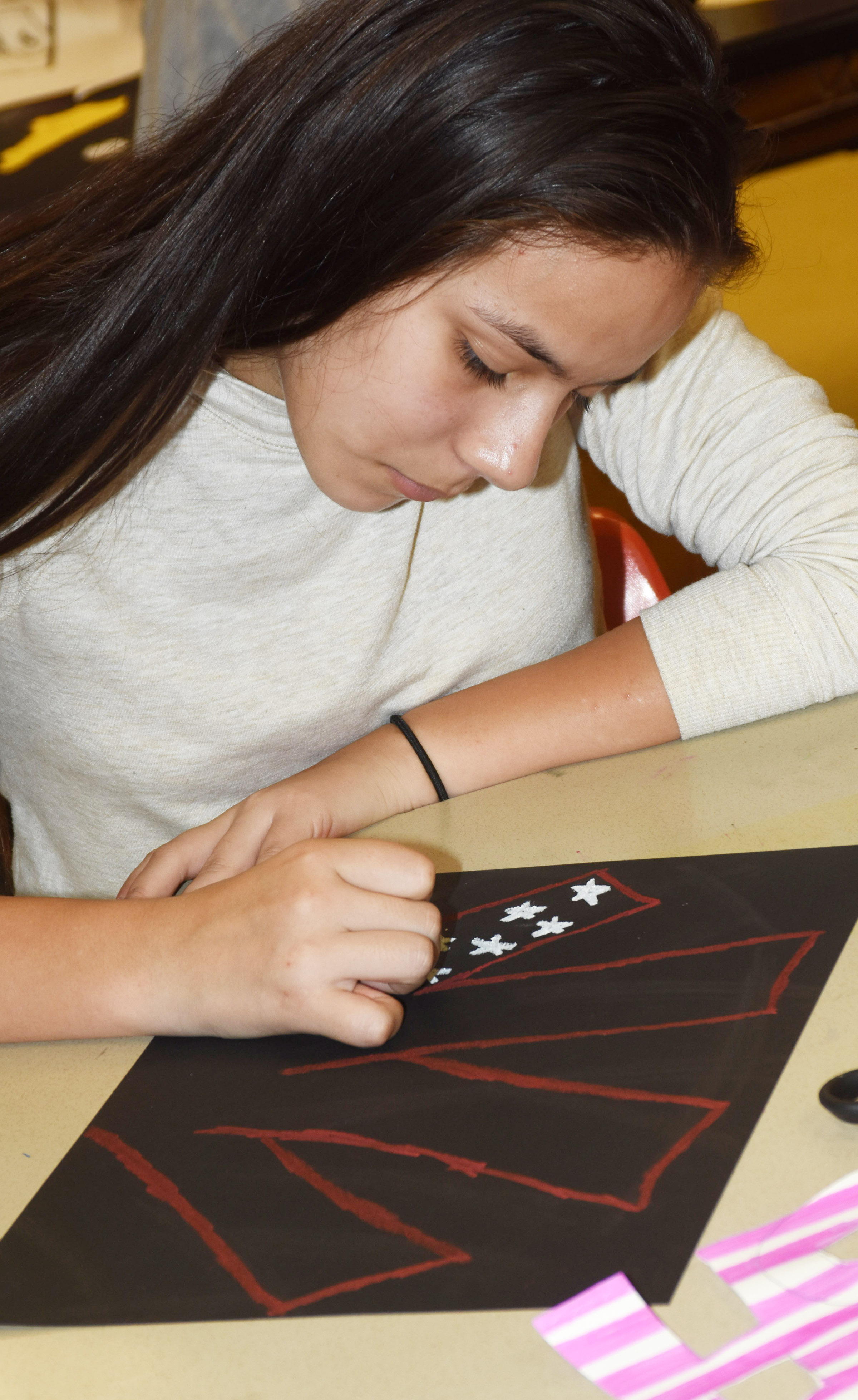 CMS sixth-grader Marissa Segura adds color to her Veterans Day artwork.