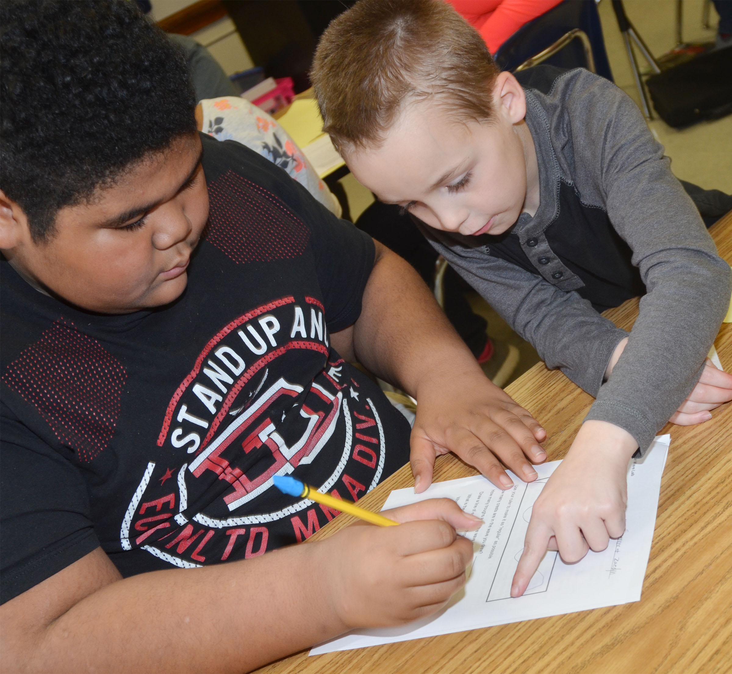 CMS fourth-graders Zaedyn Branch, at left, and Spencer Bates calculate the amplitude of the wave they drew.