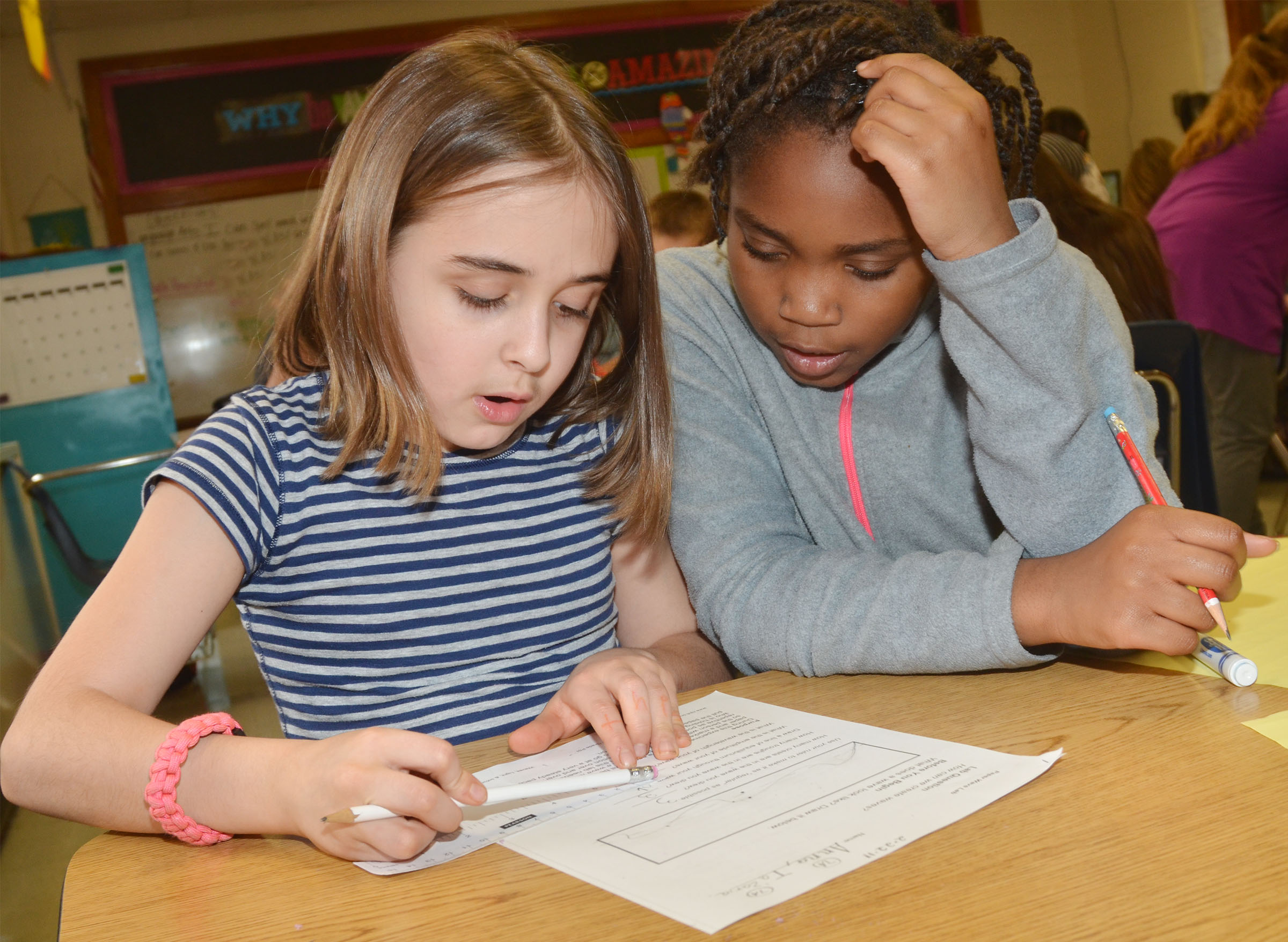 CMS fourth-graders Anna Floyd, at left, and Ta'Zaria Owens calculate the amplitude and wavelength of their waves.