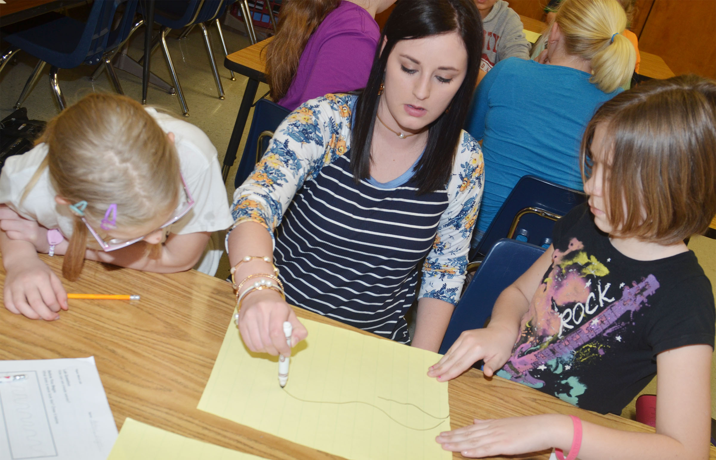 CMS fourth-grade teacher Samantha Coomer helps students Payton Releford, at left, and Isabel Dengel draw their wave.