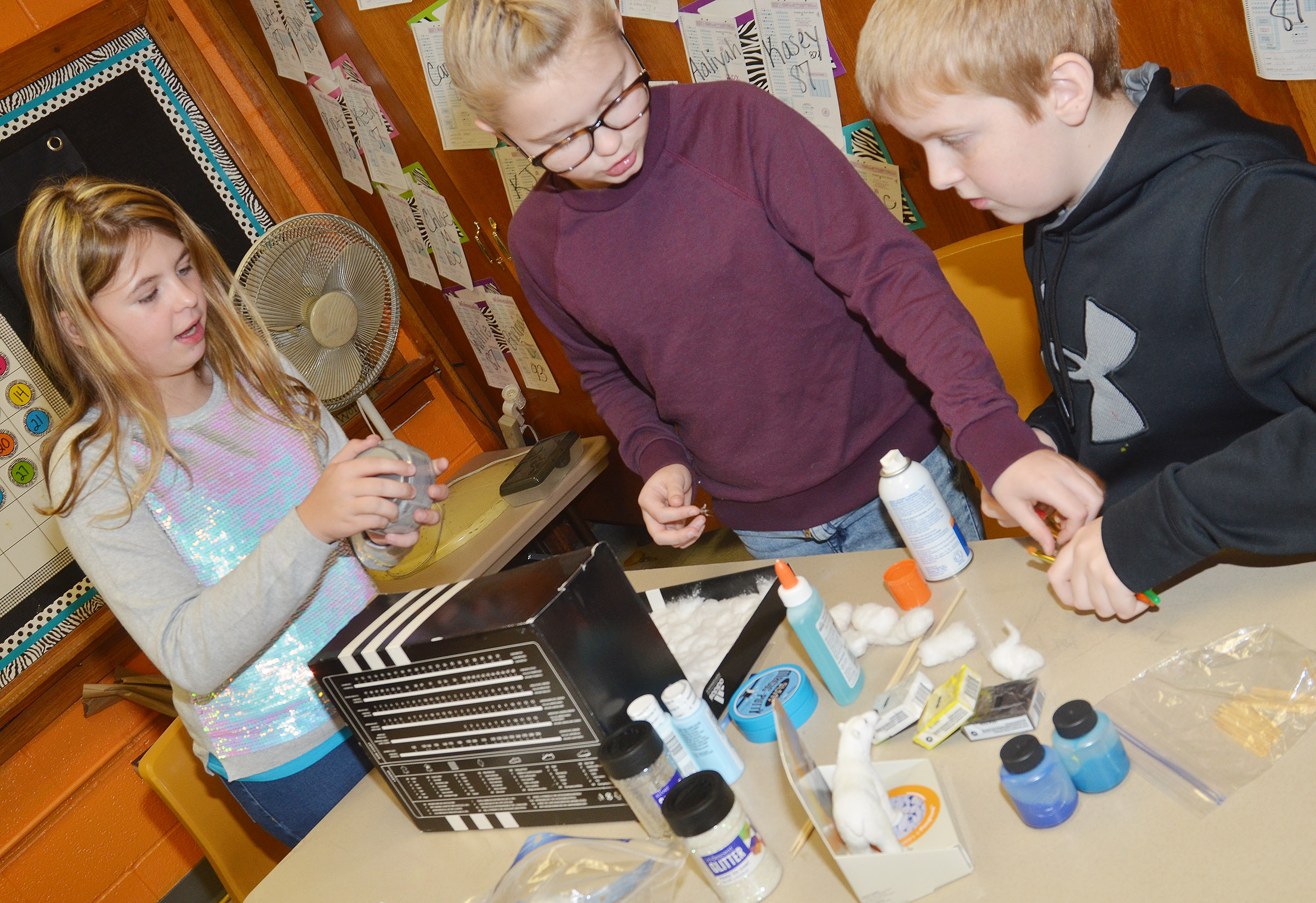 From left, CMS fifth-graders Aryanna Britton, Lillee Byrne and Ryder Cundiff use cotton to make their model of the tundra.