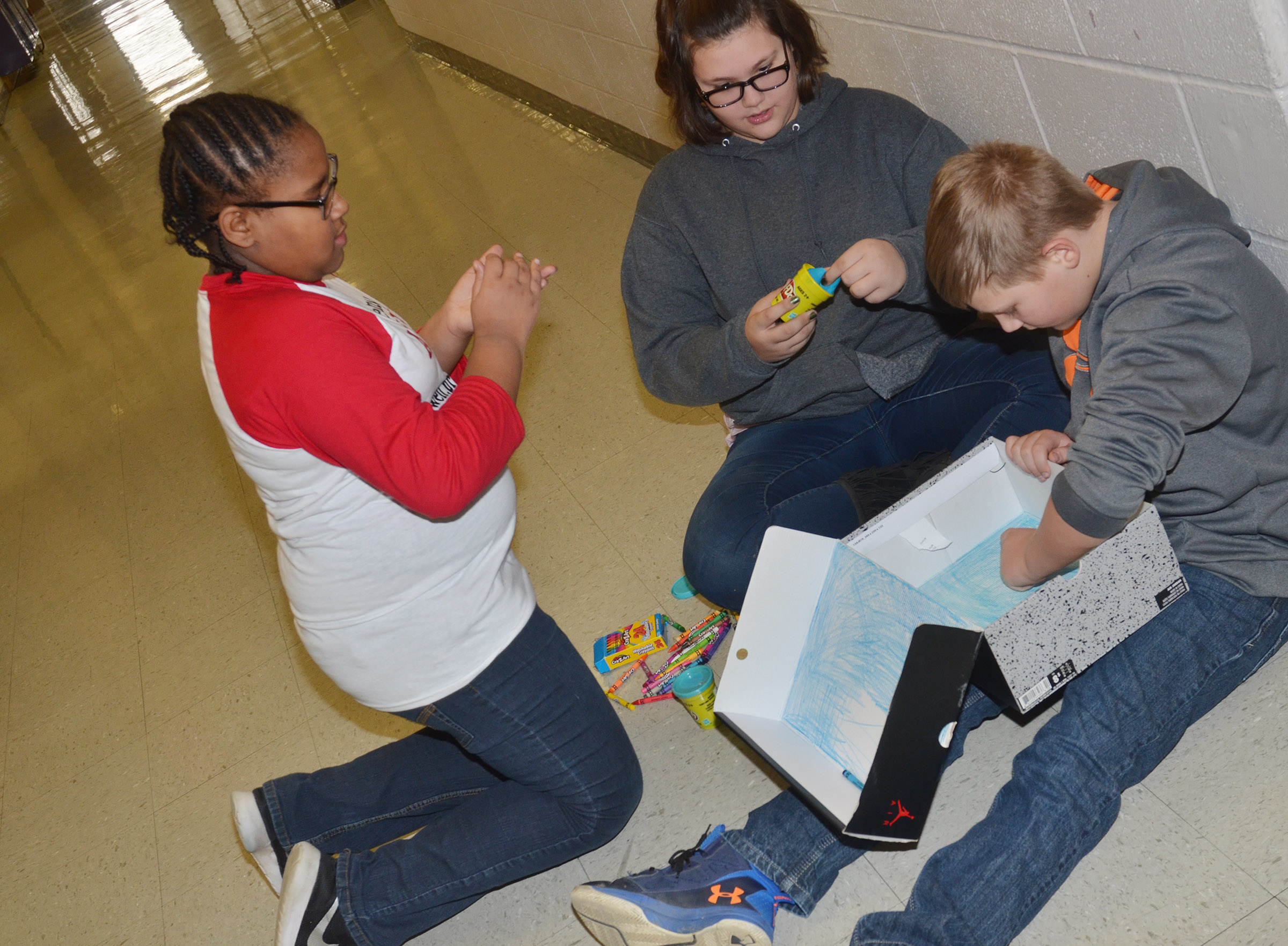 From left, CMS fifth-graders KyAshia Mitchell, Allison Sumners and Jesse King make their model.
