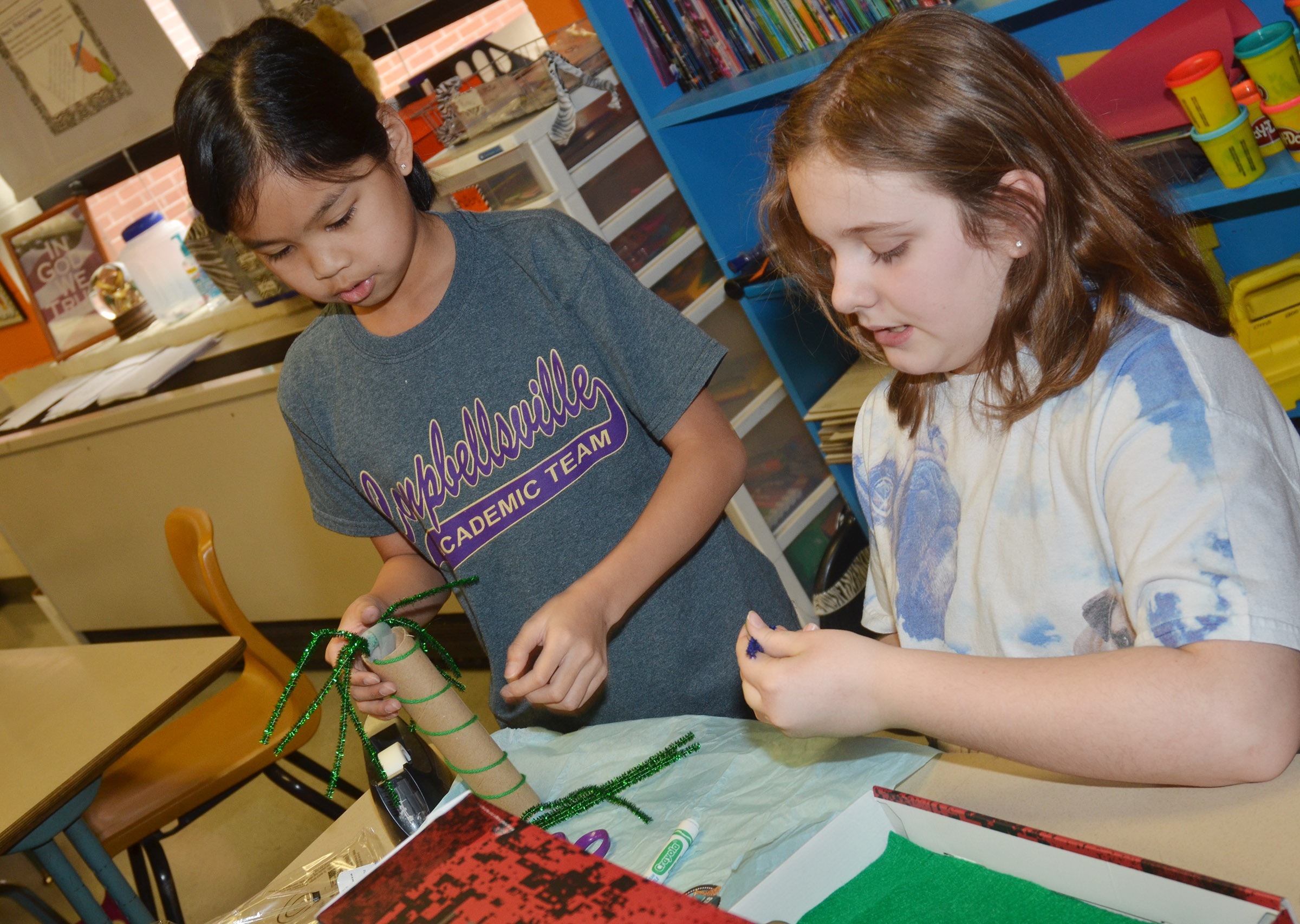 CMS fifth-graders Angelica Seng, at left, and Lexi Garvin make trees for their model.