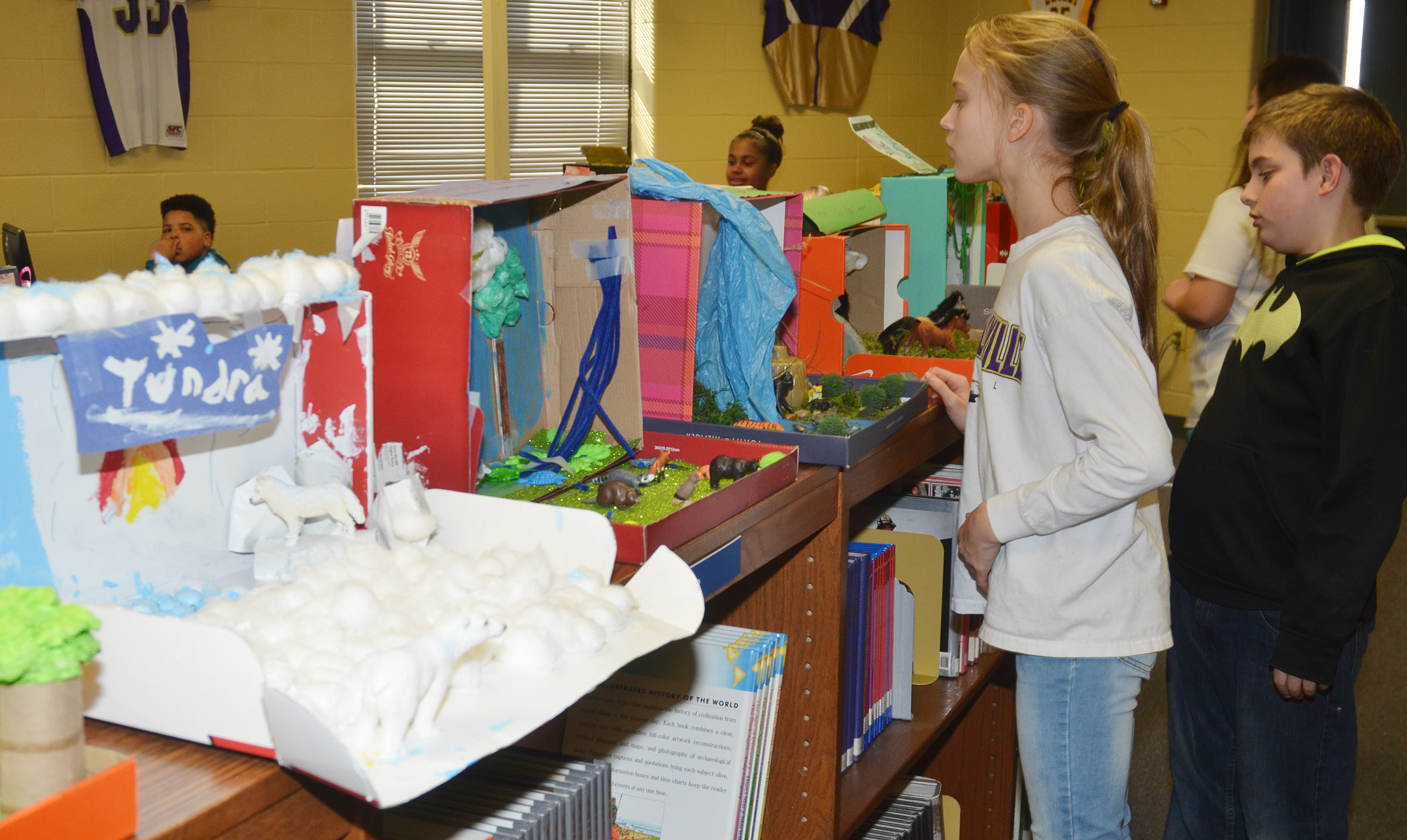 CMS students view the ecosystem models on display.