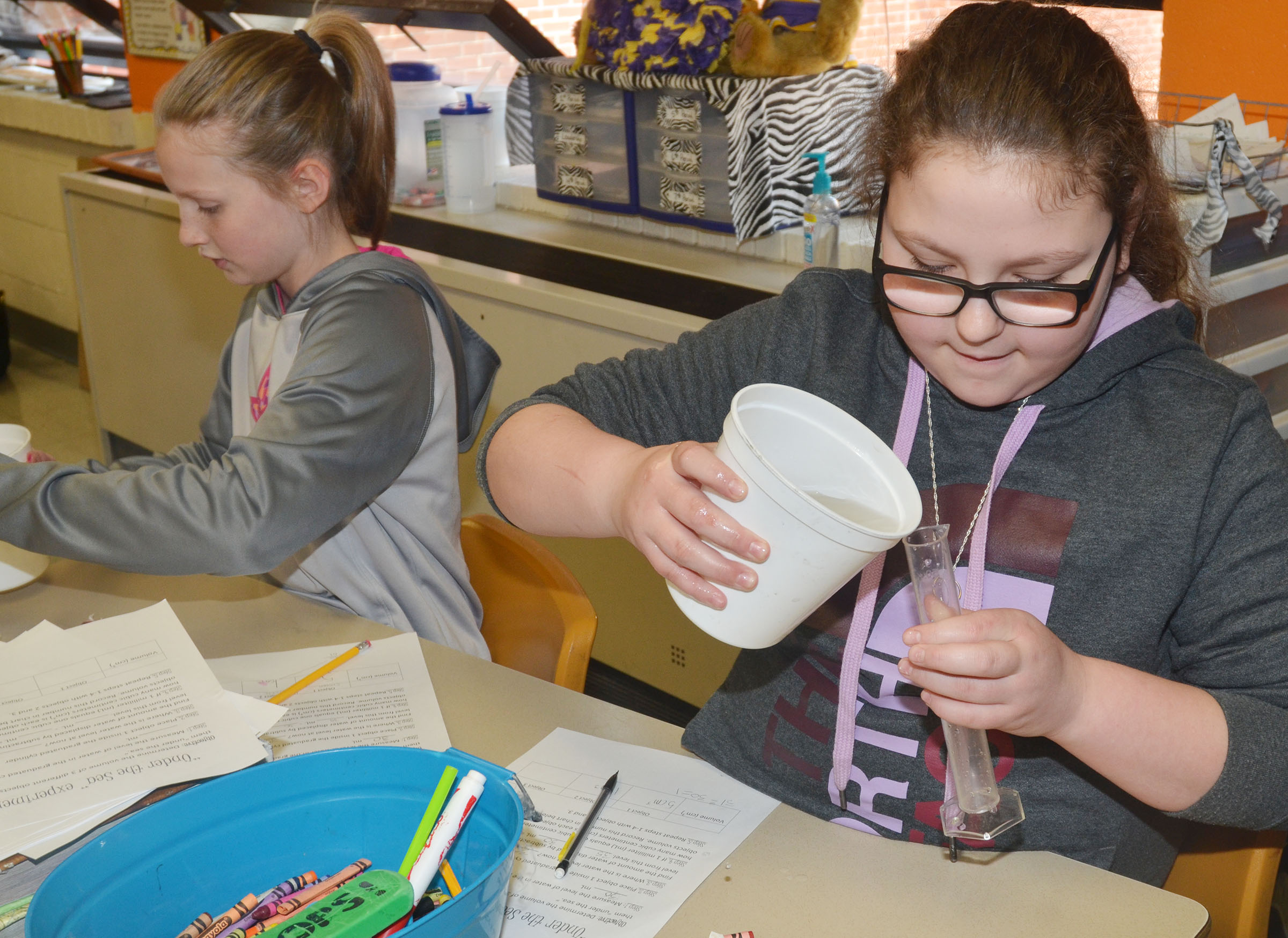 CMS fifth-grader Chloe Mitchell measures the volume of an object by placing it under water.