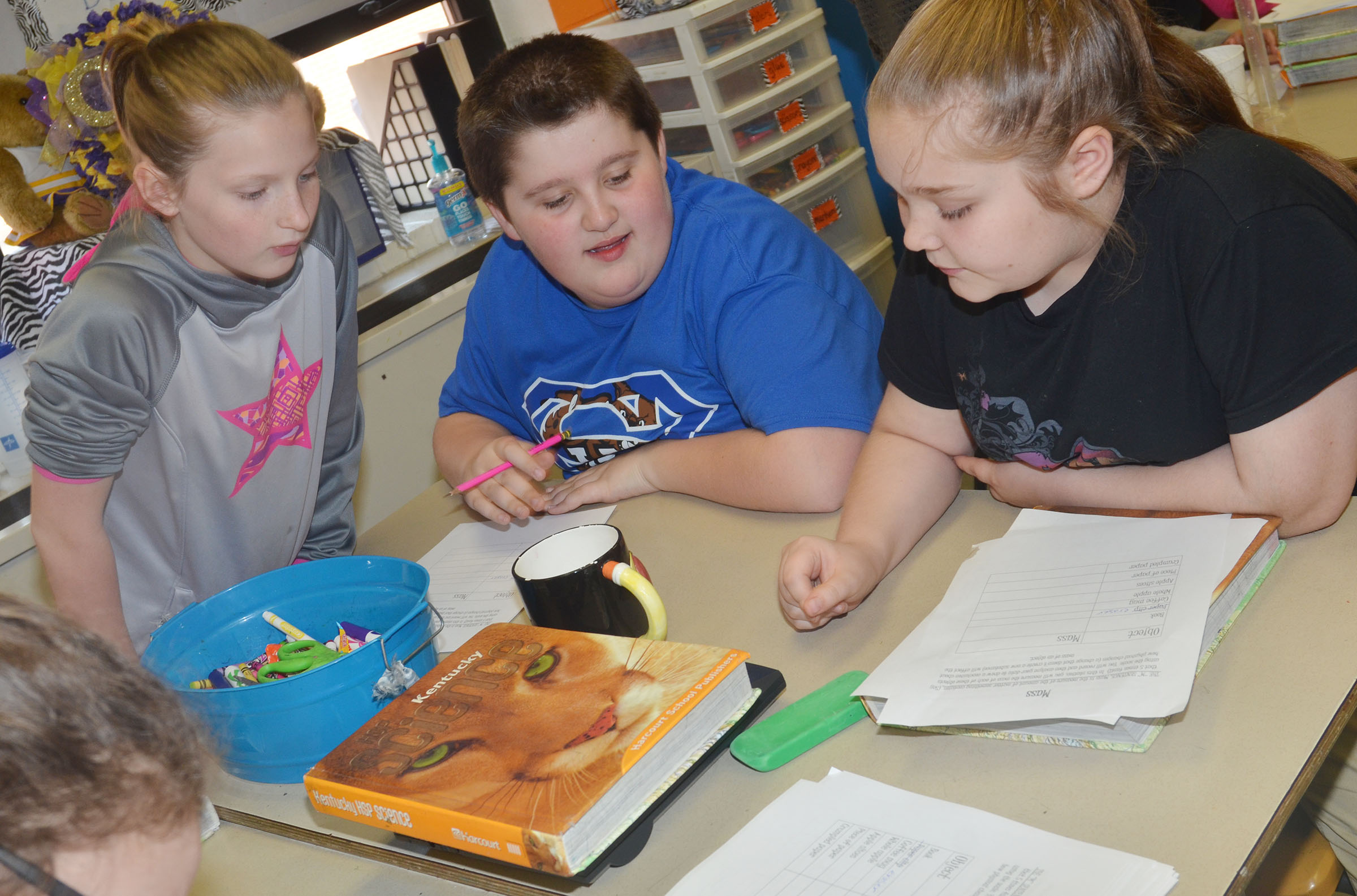 From left, CMS fifth-graders Hannah Singleton, Luke McDonald and Donna Schweickert measure the mass of a textbook.
