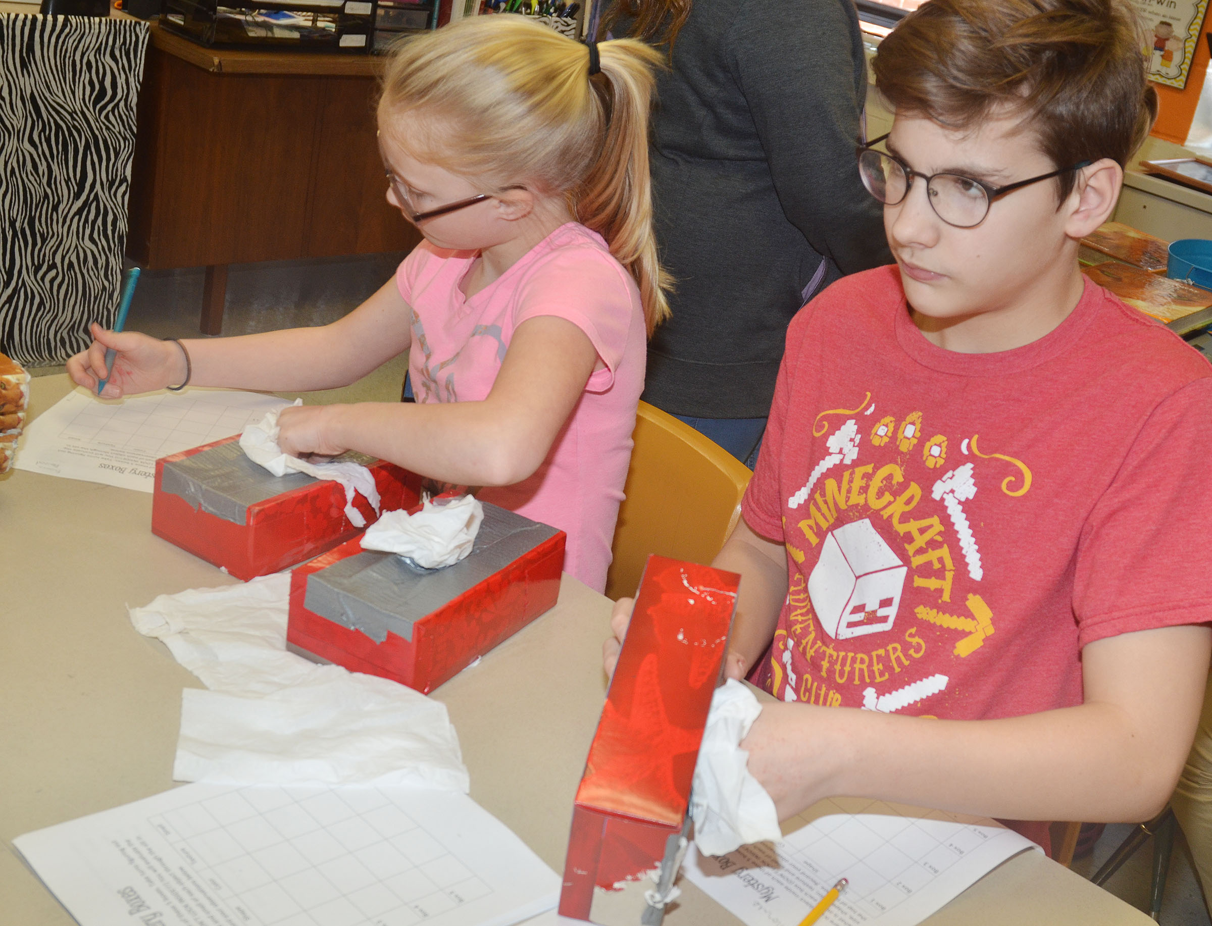 CMS fifth-graders Brianna Atwood, at left, and Dalton Morris see if they can identify an object based on its physical characteristics.