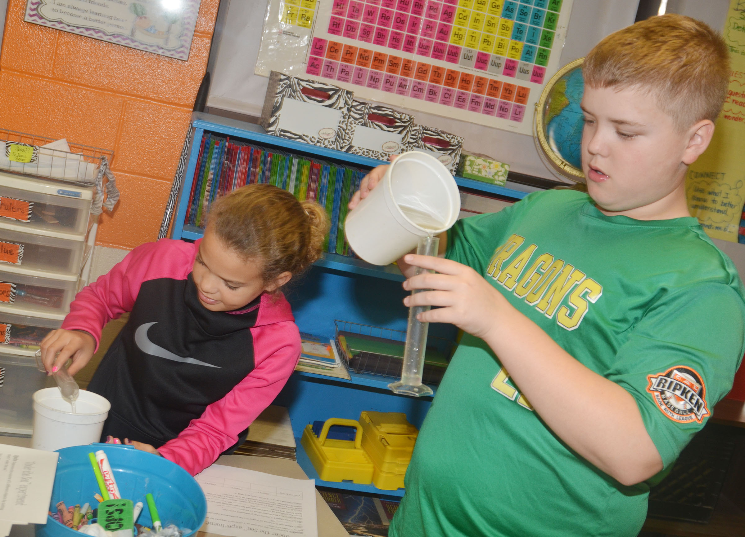 CMS fifth-graders Arisha Francis, at left, and Ryan Grubbs measure the volume of an object by placing it under water.