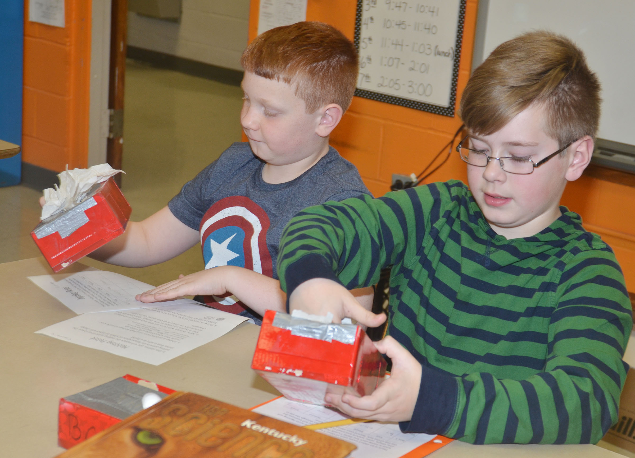 CMS fifth-graders Conner Rinehart, at left, and Jovi Bowen see if they can identify an object based on its physical characteristics.