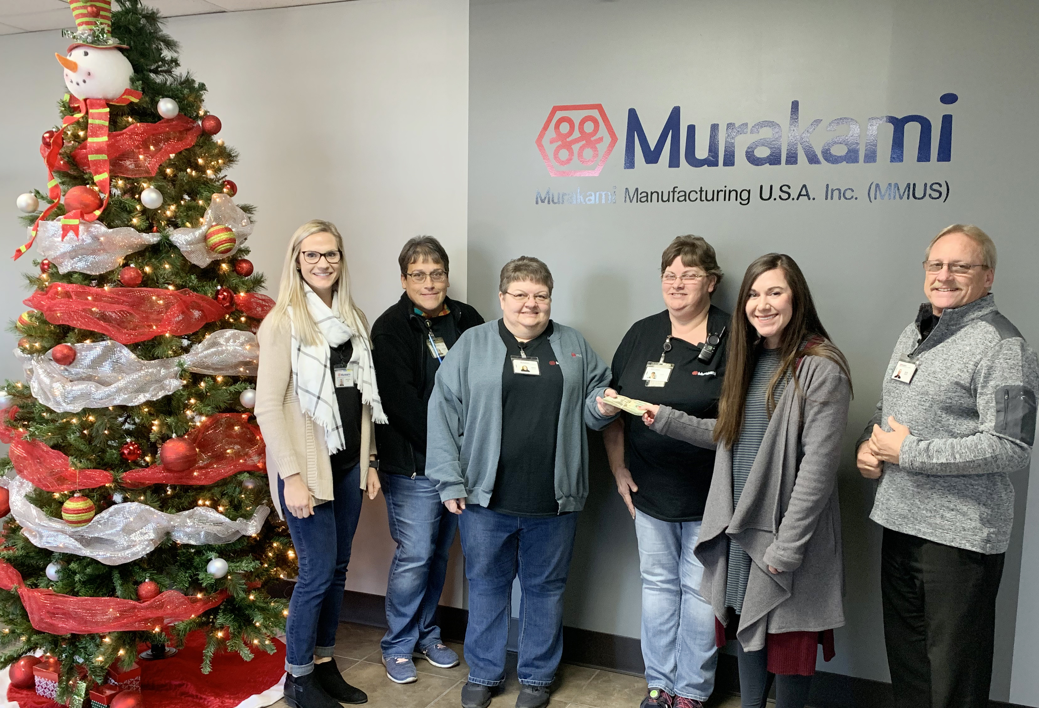 Campbellsville Family Resource and Youth Services Center recently received a $1,000 donation from Murakami Manufacturing USA to help Campbellsville Independent Schools' students. Accepting the donation from Murakami employees is FRYSC Director Courtney Sowell, fifth from left.