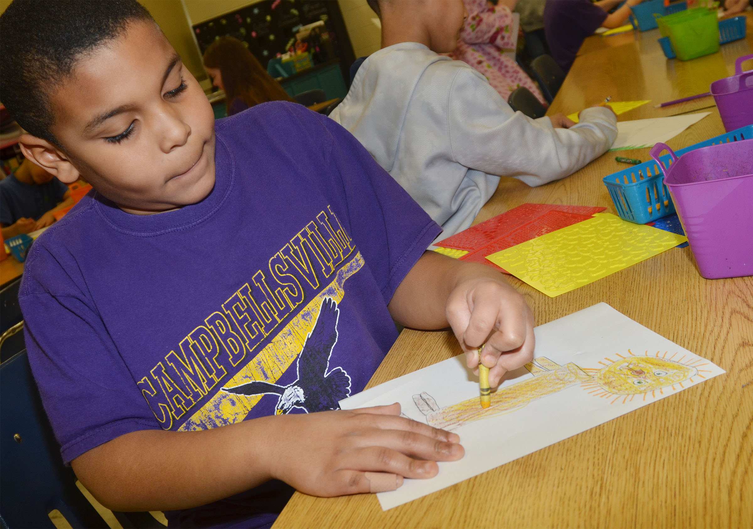 CES second-grader Zaemar Hoskins colors his lion drawing.
